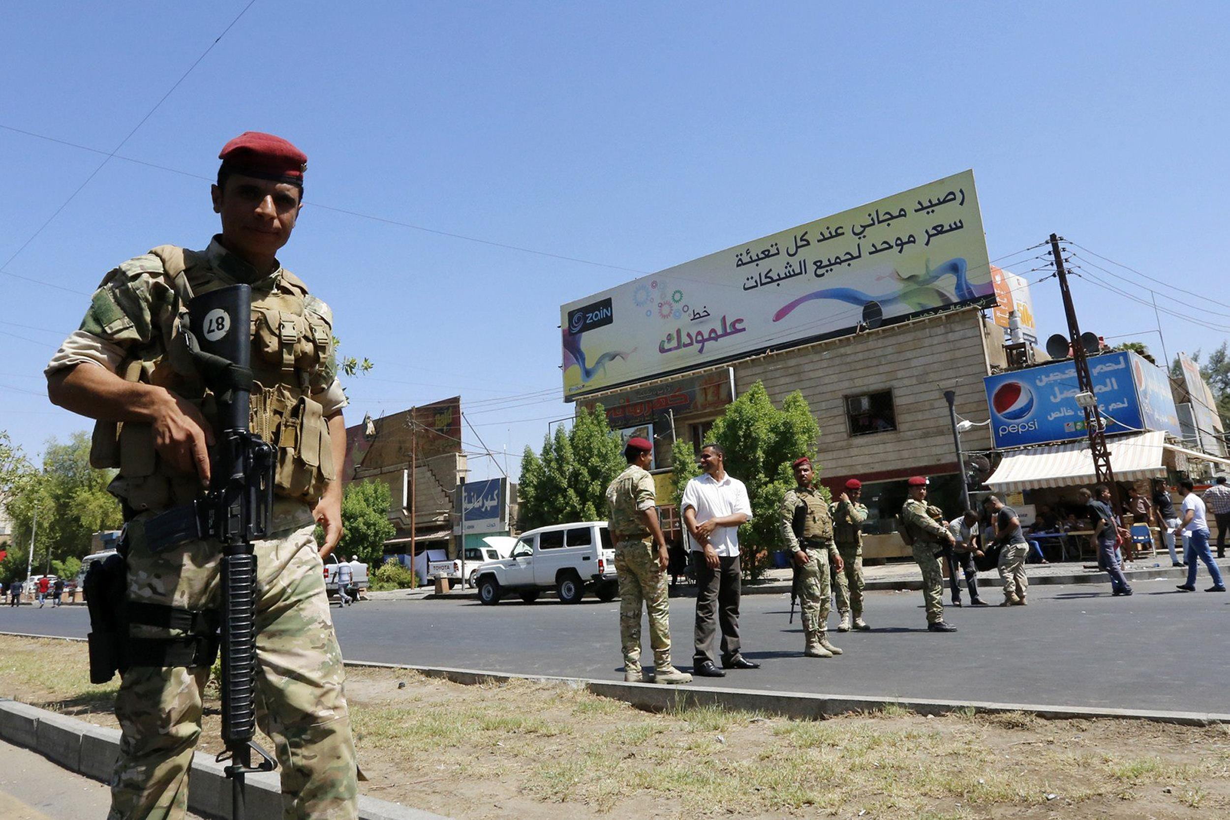 Image: Iraqi security forces patrol a street in Baghdad's commercial district