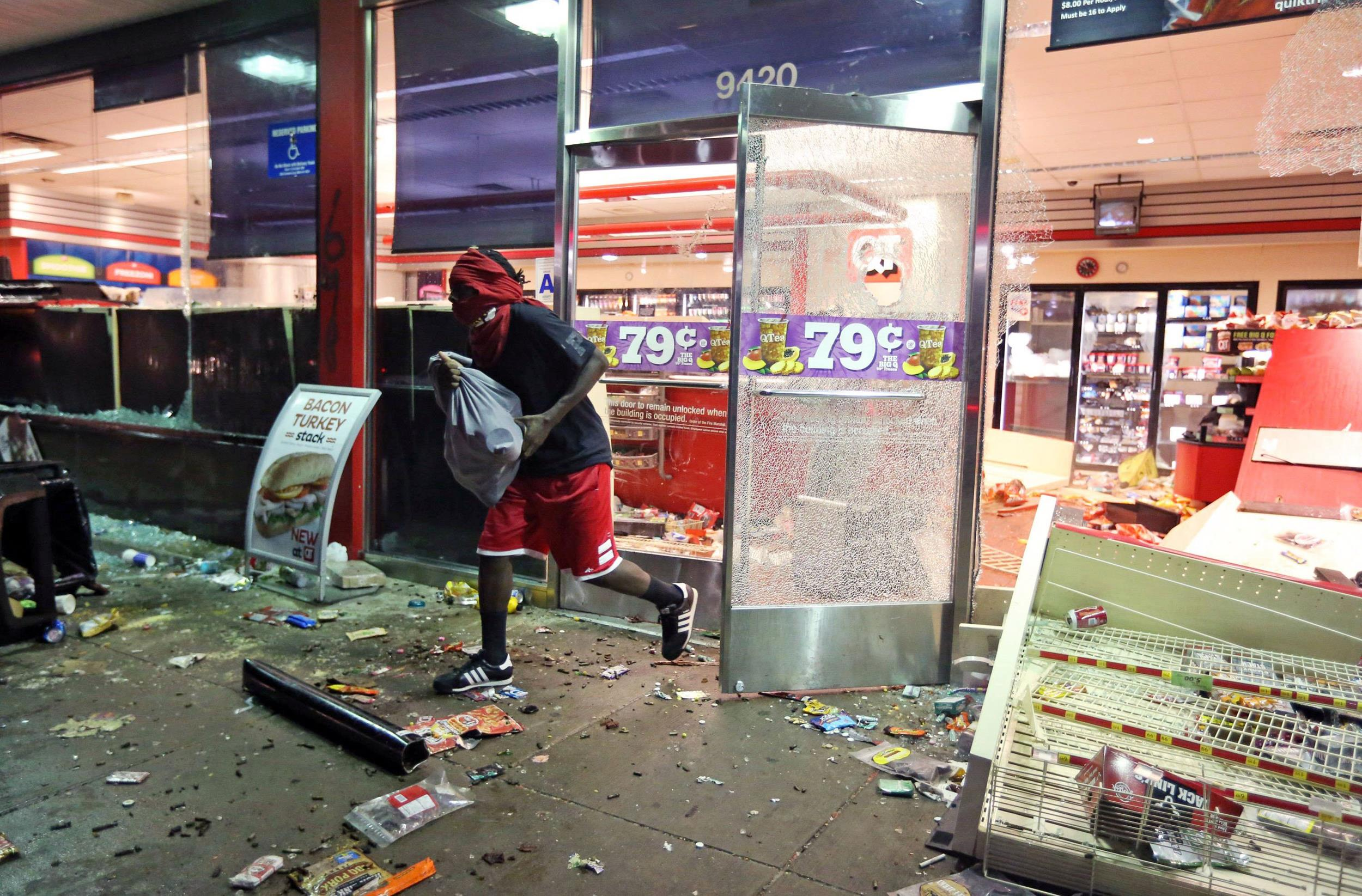 Image: A man leaves a store on Sunday, Aug. 10, 2014, in Ferguson, Mo.
