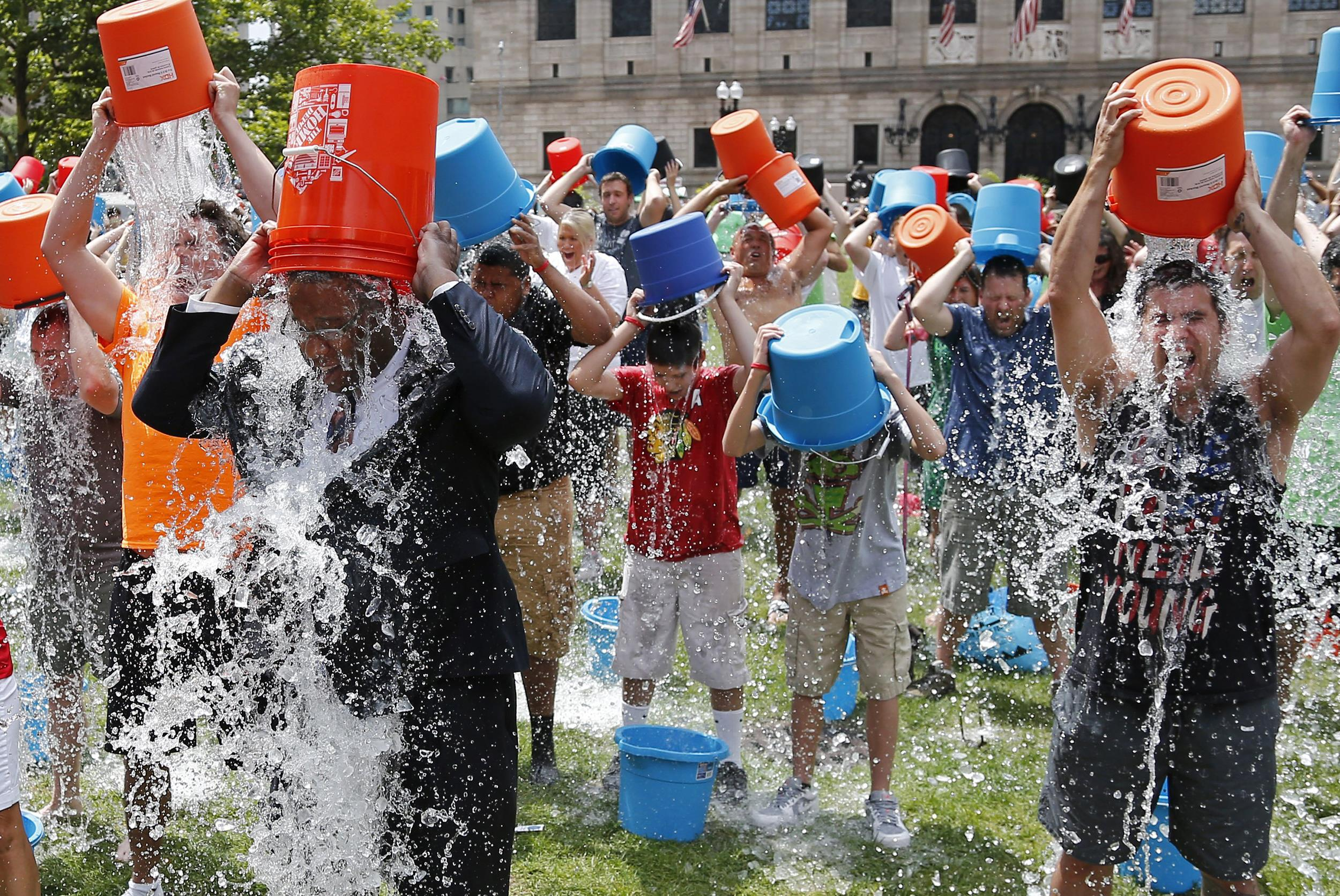 Image: Boston City Councillor Tito Jackson, left in suit, leads some 200 people in the ice bucket challenge at Boston's Copley Square, on Aug. 7