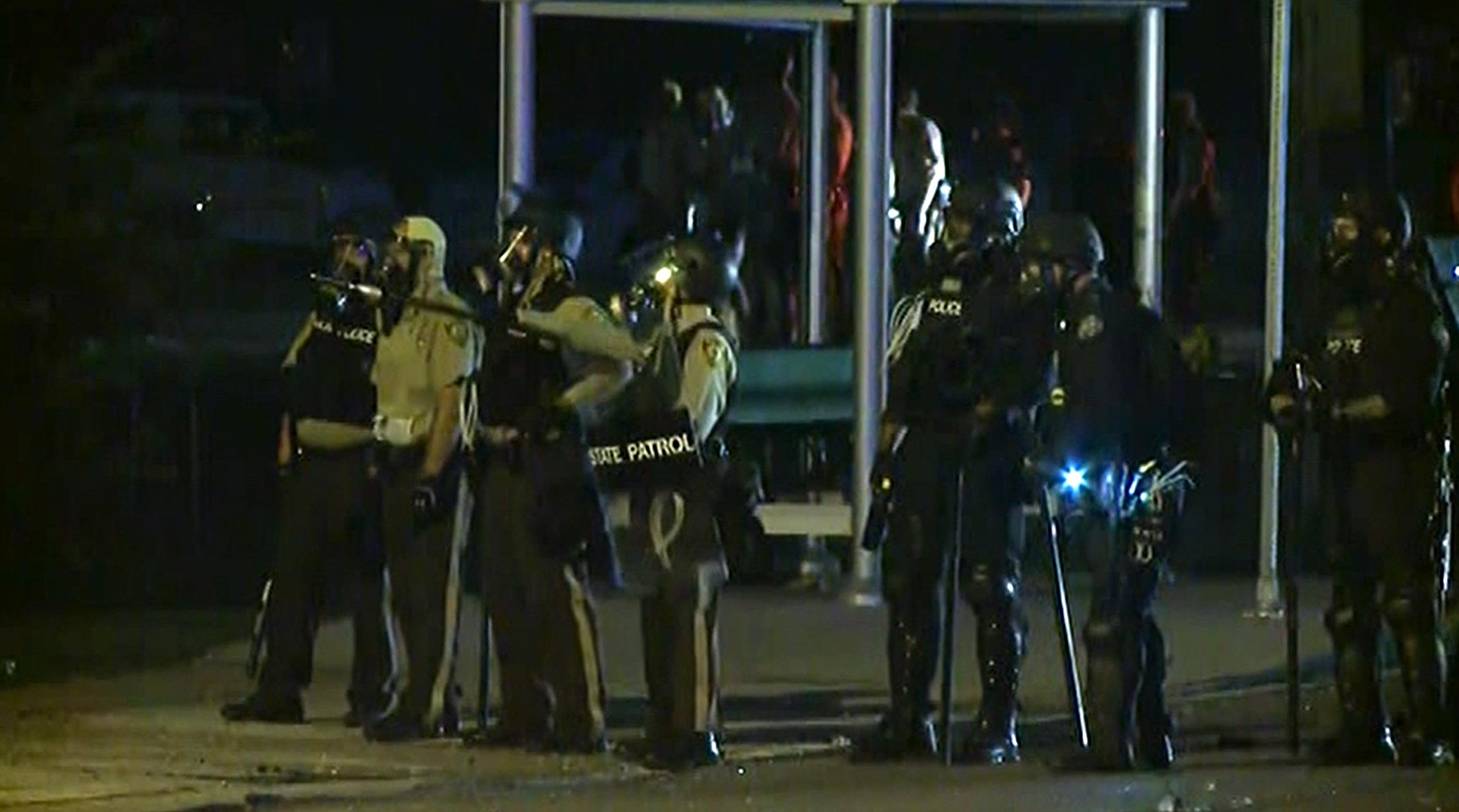 Image: Police in riot gear stand on a street in Ferguson, Mo., as people continued to react to the death of 18-year-old Michael Brown