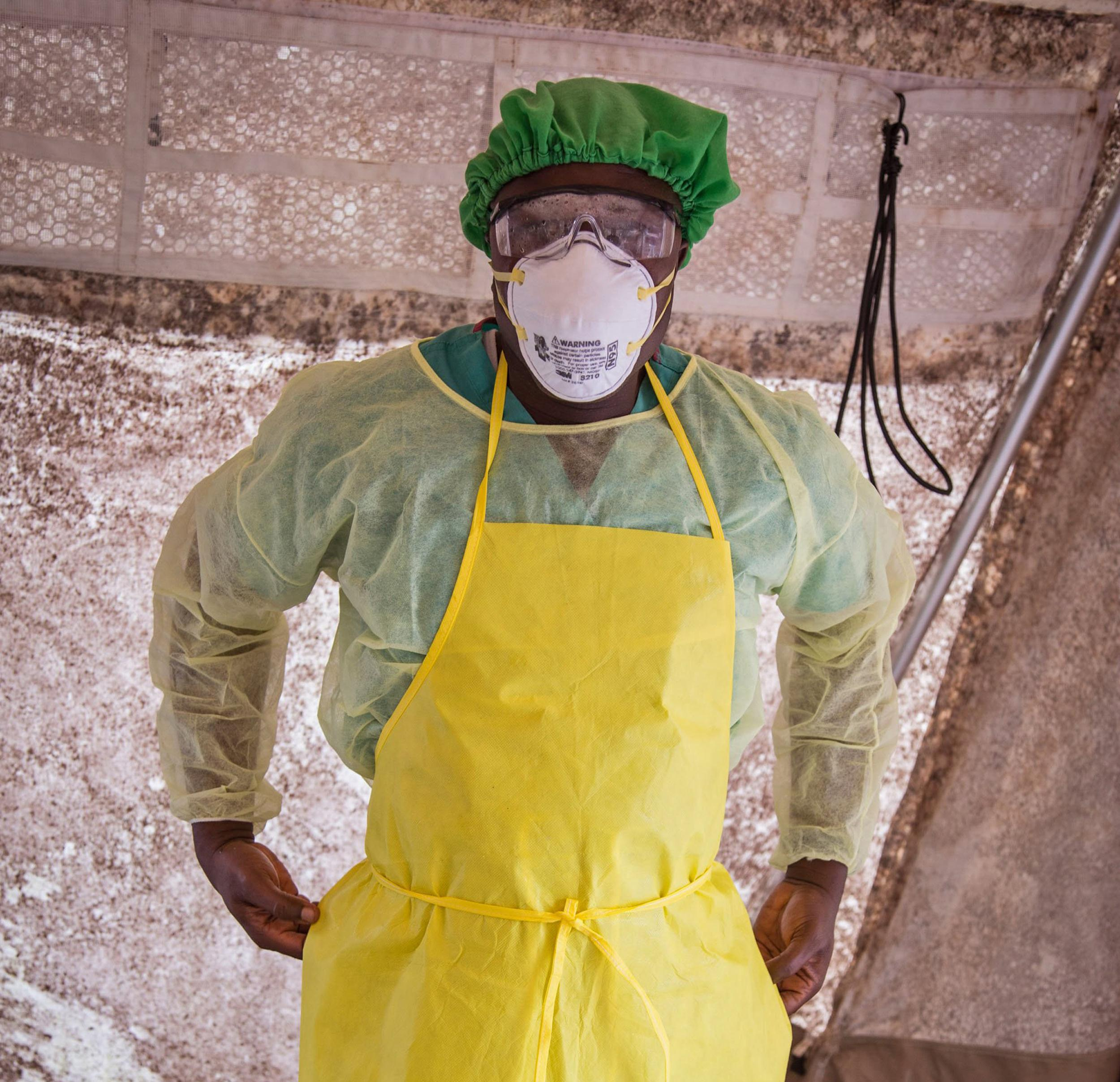 Image: A health worker prepares to examine patients for Ebola