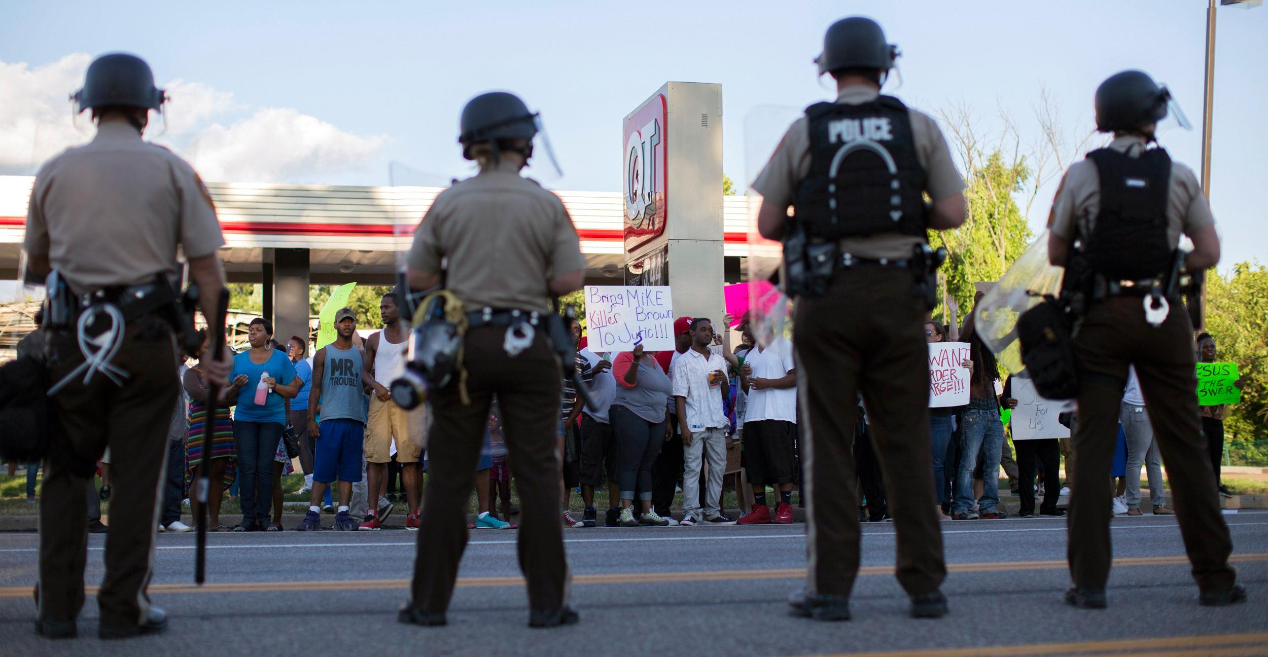 Image: Police officers watch as demonstrators protest the death of black teenager Michael Brown in Ferguson