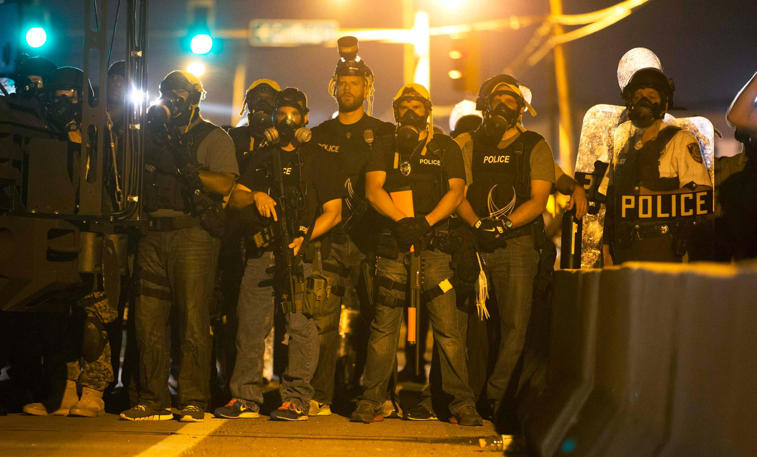 Image: Police officers keep watch while demonstrators protest the death of black teenager Michael Brown in Ferguson