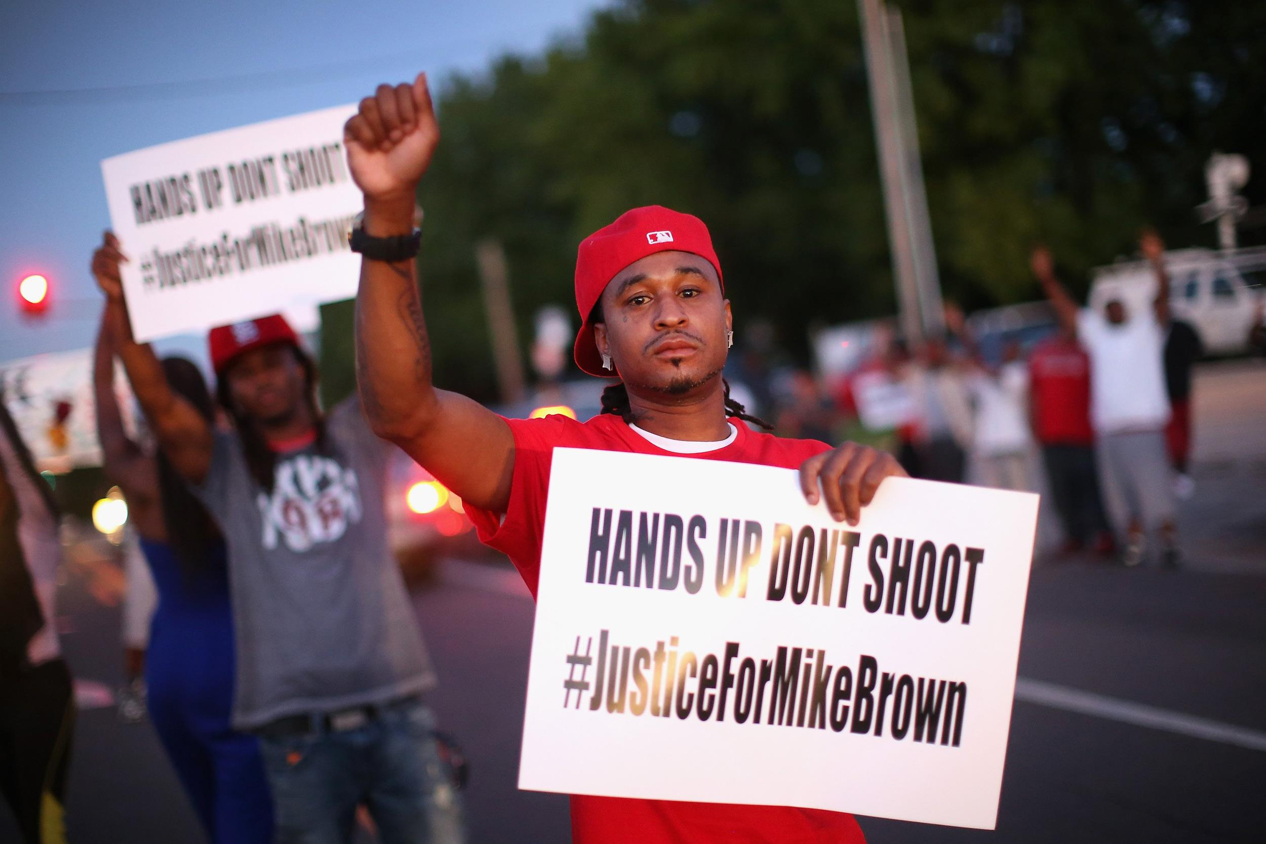 Image: Demonstrators protest the killing of teenager Michael Brown outside Greater St. Marks Family Church