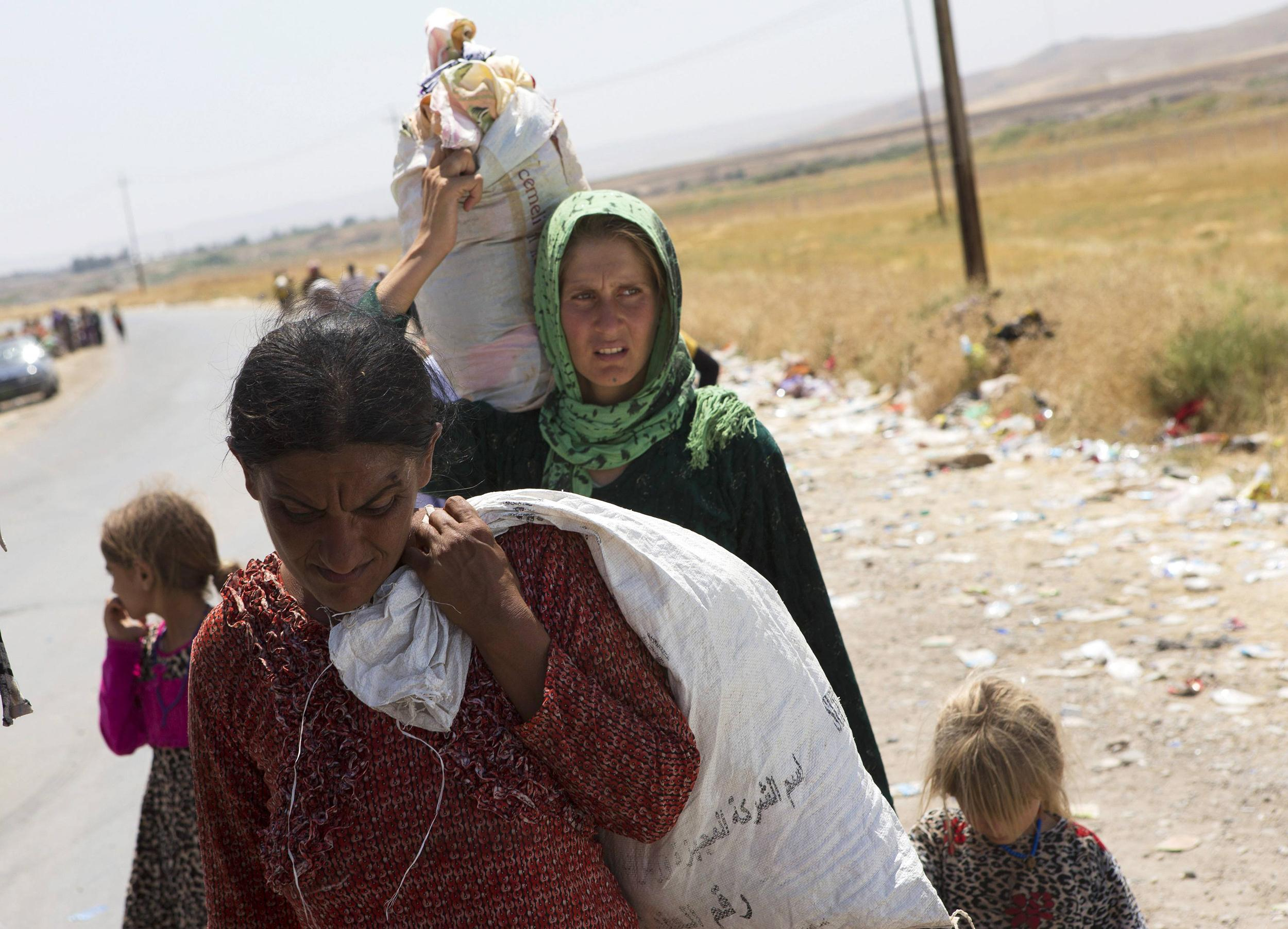 Image: Displaced people from the minority Yazidi sect, fleeing the violence in the Iraqi town of Sinjar, re-enter Iraq from Syria at the Iraqi-Syrian border crossing in Fishkhabour