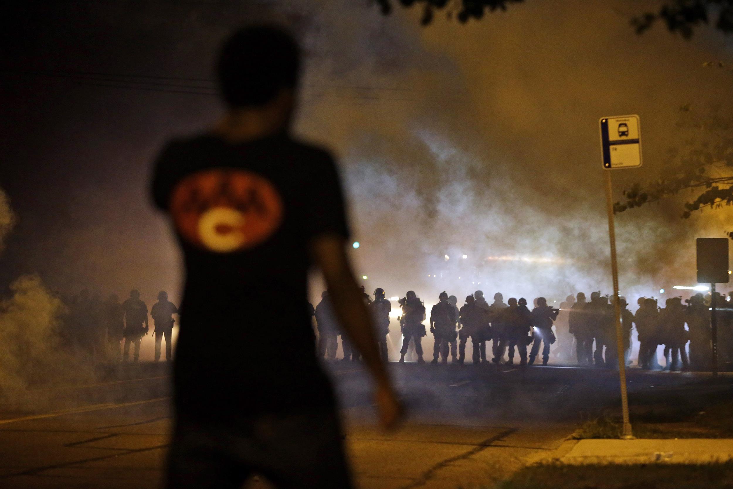 Image: A man watches as police walk through a cloud of smoke during a clash with protesters