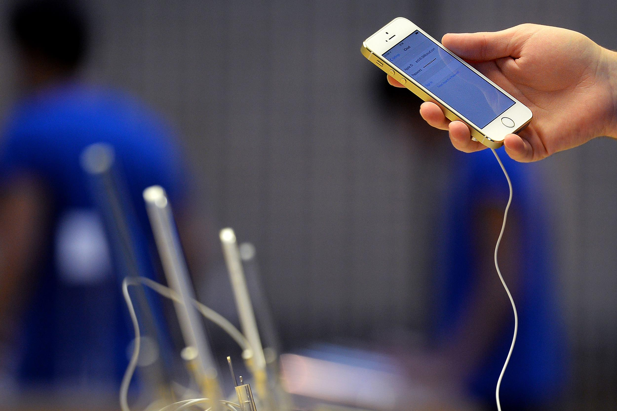 Image: An employee prepares a display iPhone 5S at the Apple store