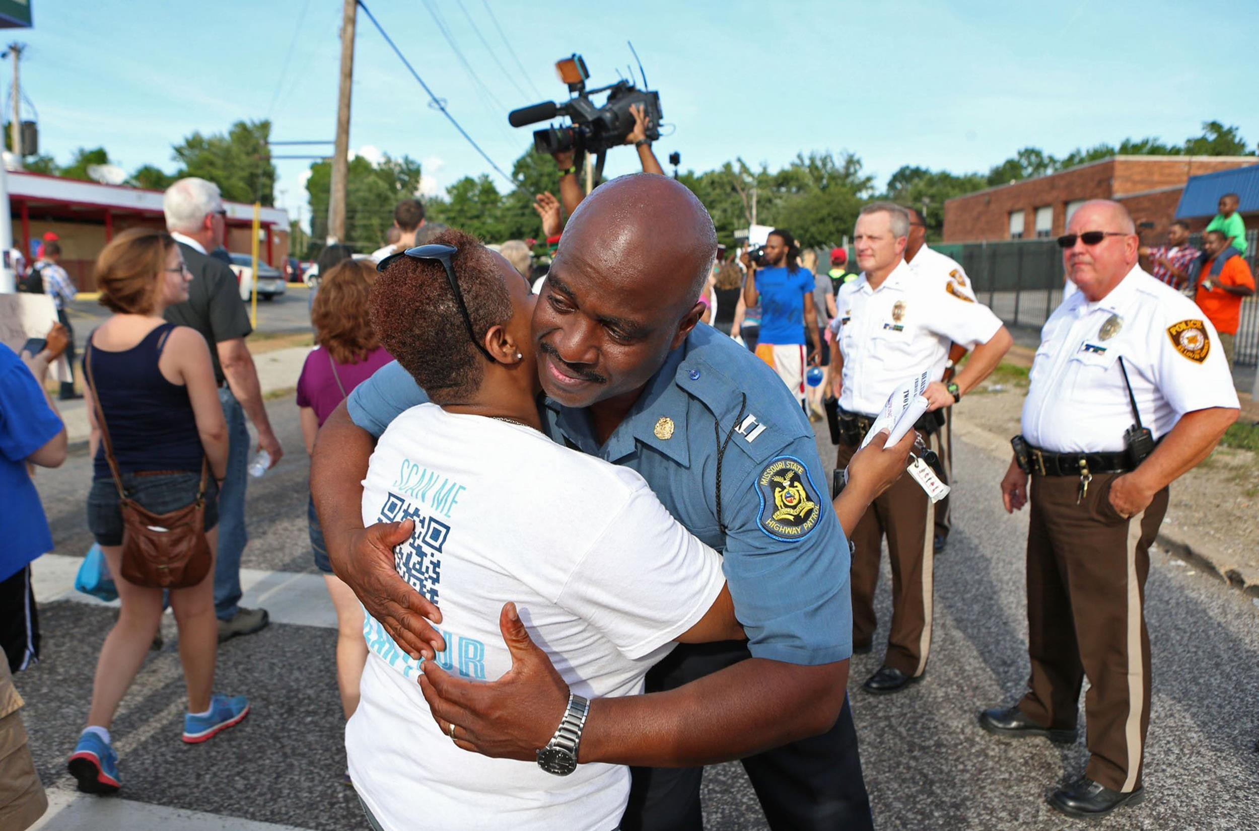 Image: Capt. Ronald Johnson of the Missouri Highway Patrol hugs Angela Whitman, of Berkeley, Mo., on West Florissant Avenue in Ferguson, Mo.