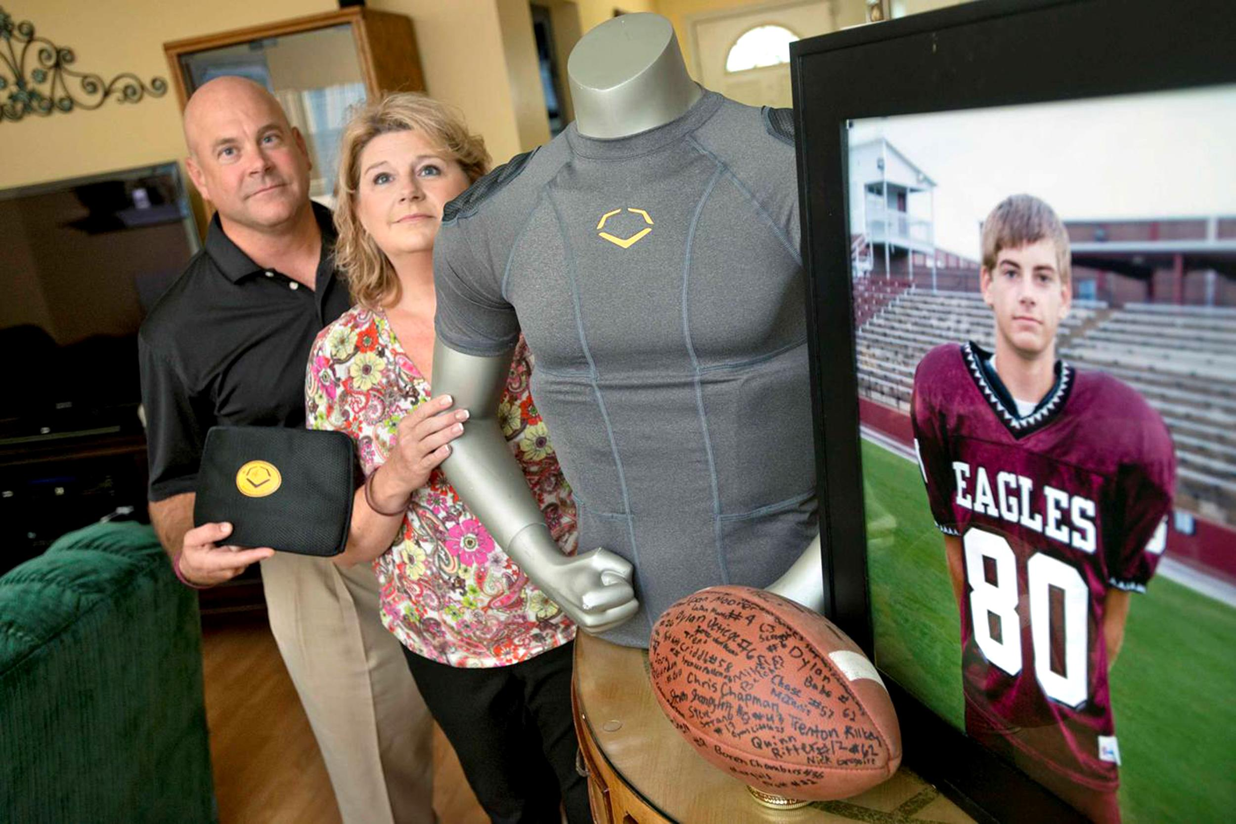 Image: Brian and Kathy Haugen with a photo of their son, Taylor, who died at 15 of a crushed liver after a football hit.
