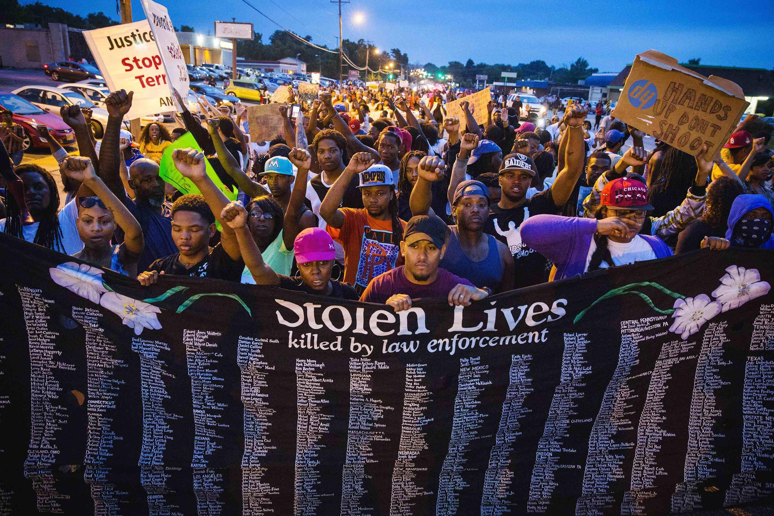 Image: Protestors march and hold their fists aloft as they march during ongoing demonstrations in reaction to the shooting of Michael Brown in Ferguson, Missouri