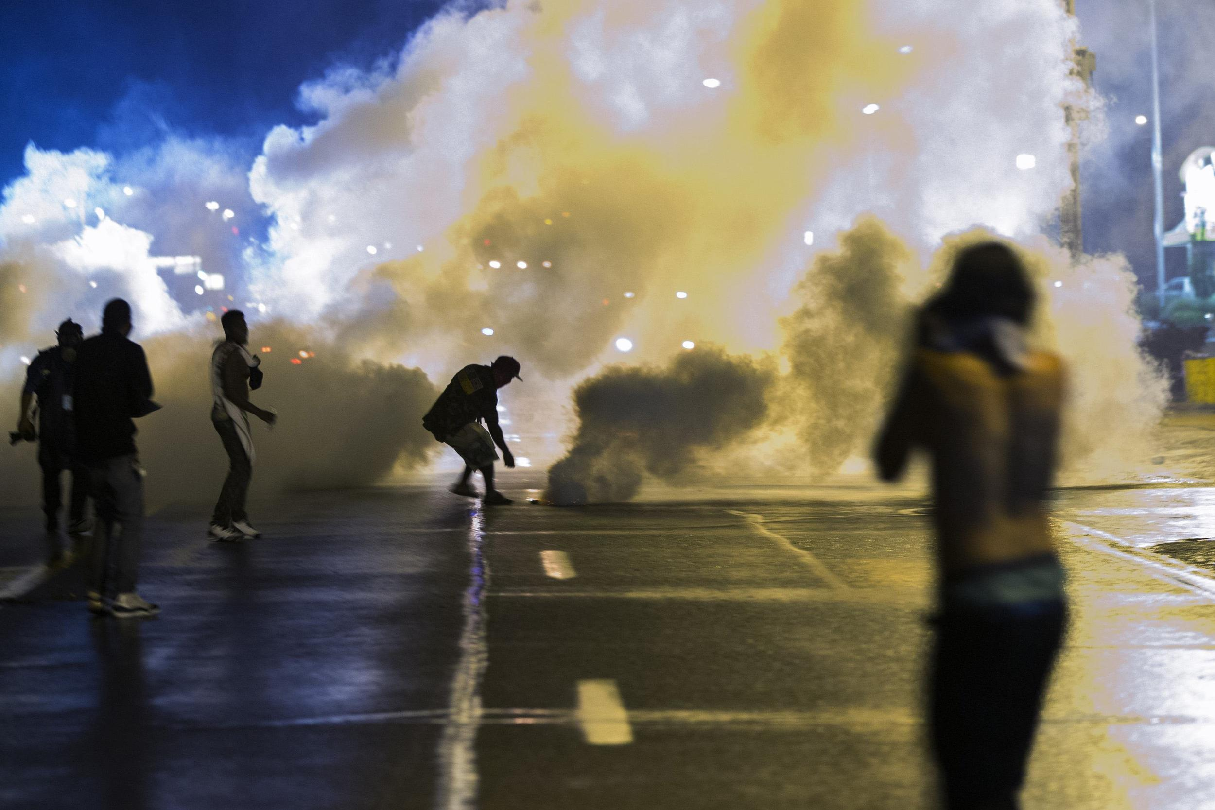Image: A protester reaches down to throw back a smoke canister as police clear a street after the passing of a midnight curfew in Ferguson