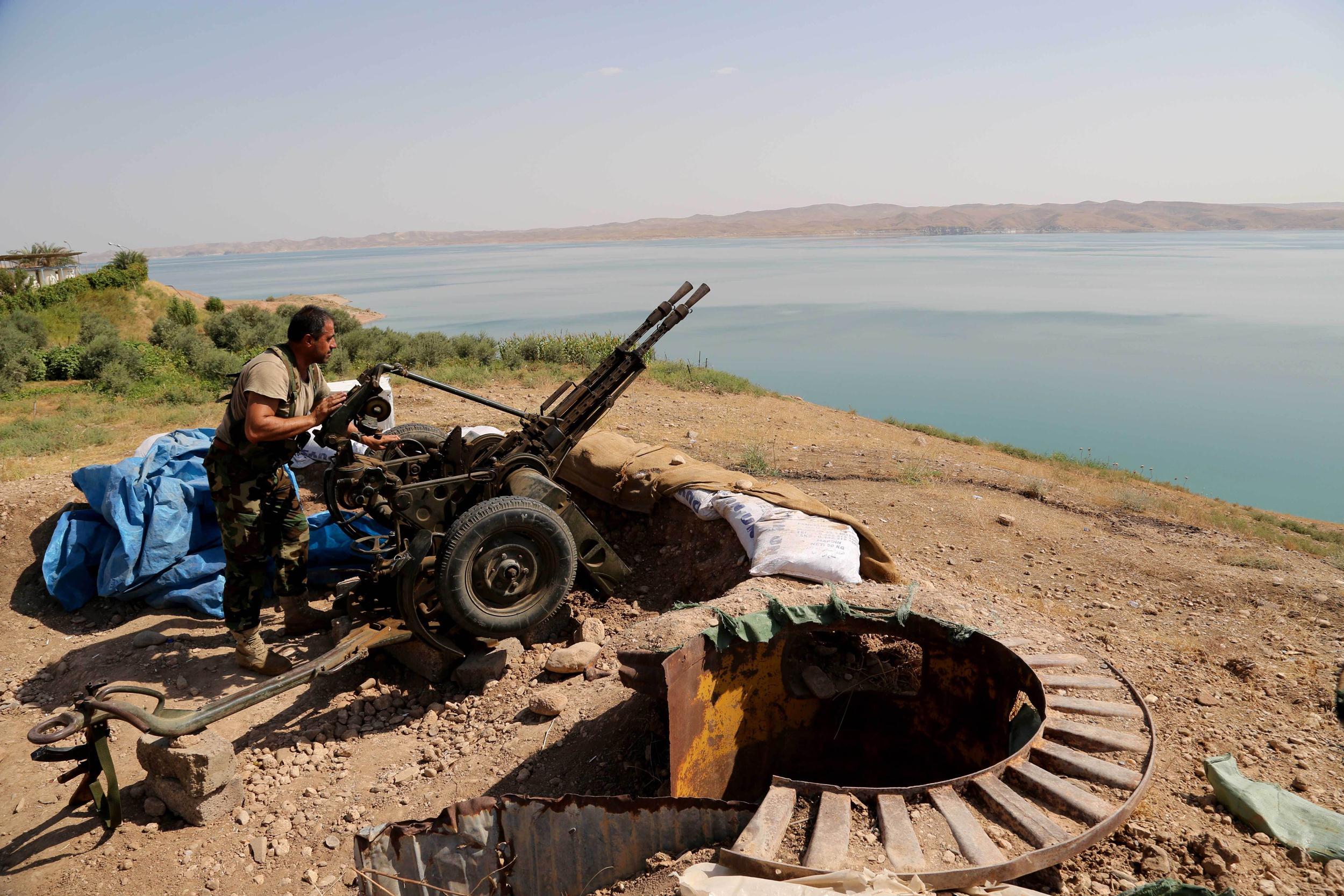 Image: A Kurdish peshmerga fighter prepares his weapon at his combat position near the Mosul Dam