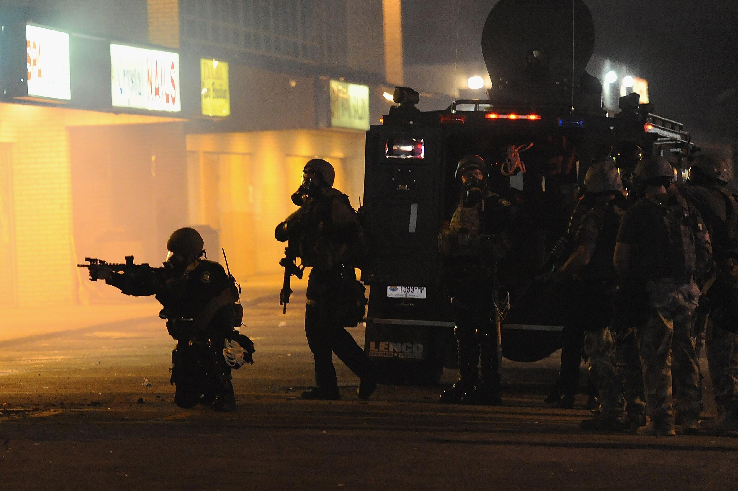 Image: Police officers fire canisters of tear gas on protestors as they try to flee from West Florissant Road