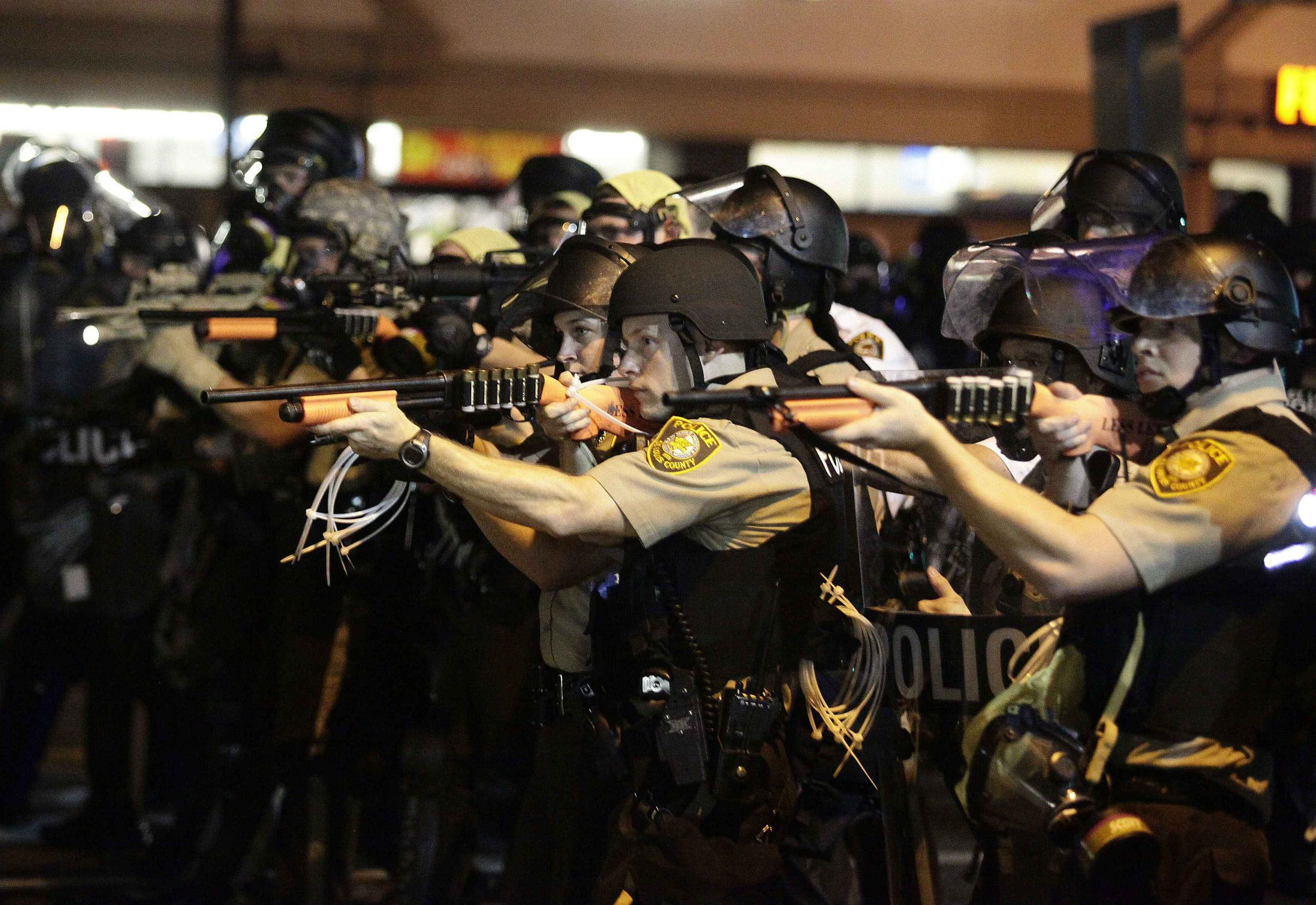 Image: Police officers point their weapons at demonstrators protesting against the shooting death of Michael Brown in Ferguson, Missouri