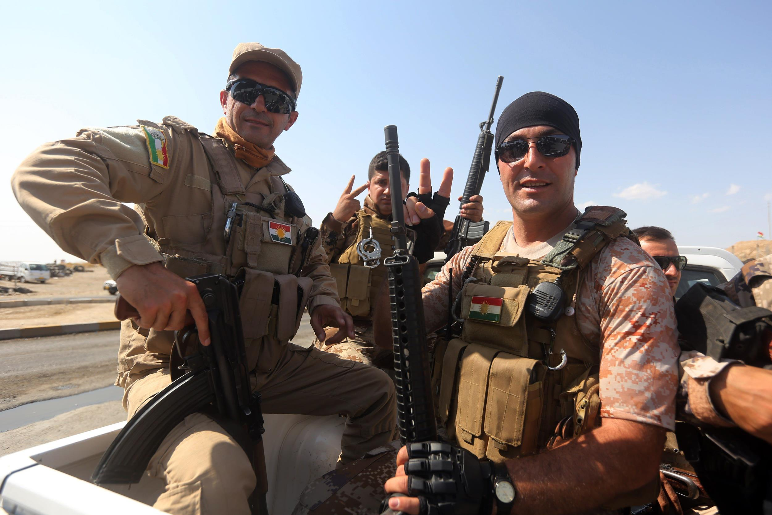 Image: Kurdish peshmerga fighters flash the sign for victory