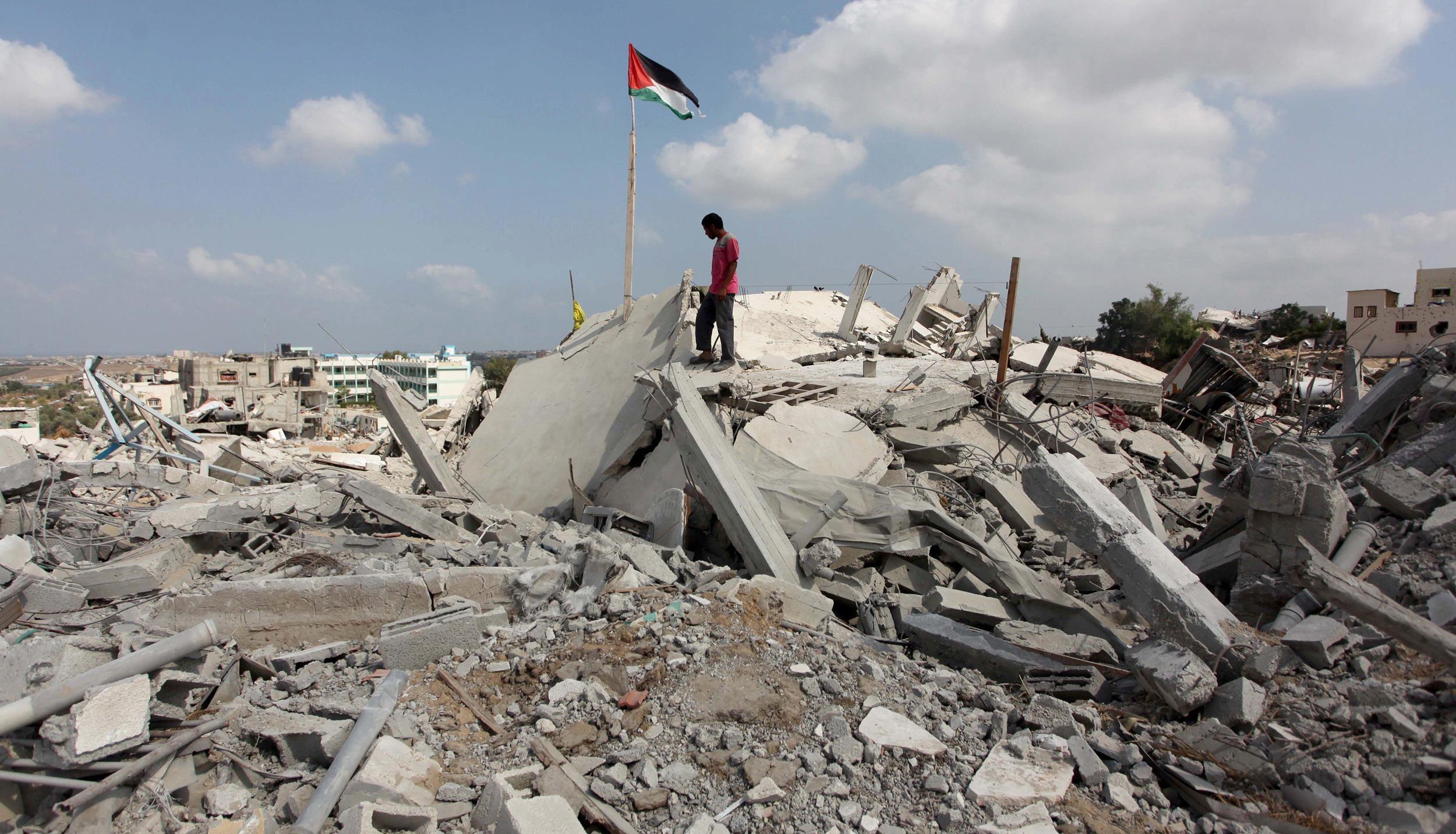 Image: Palestinians among the destroyed buildings in Gaza's Johr al-Deek