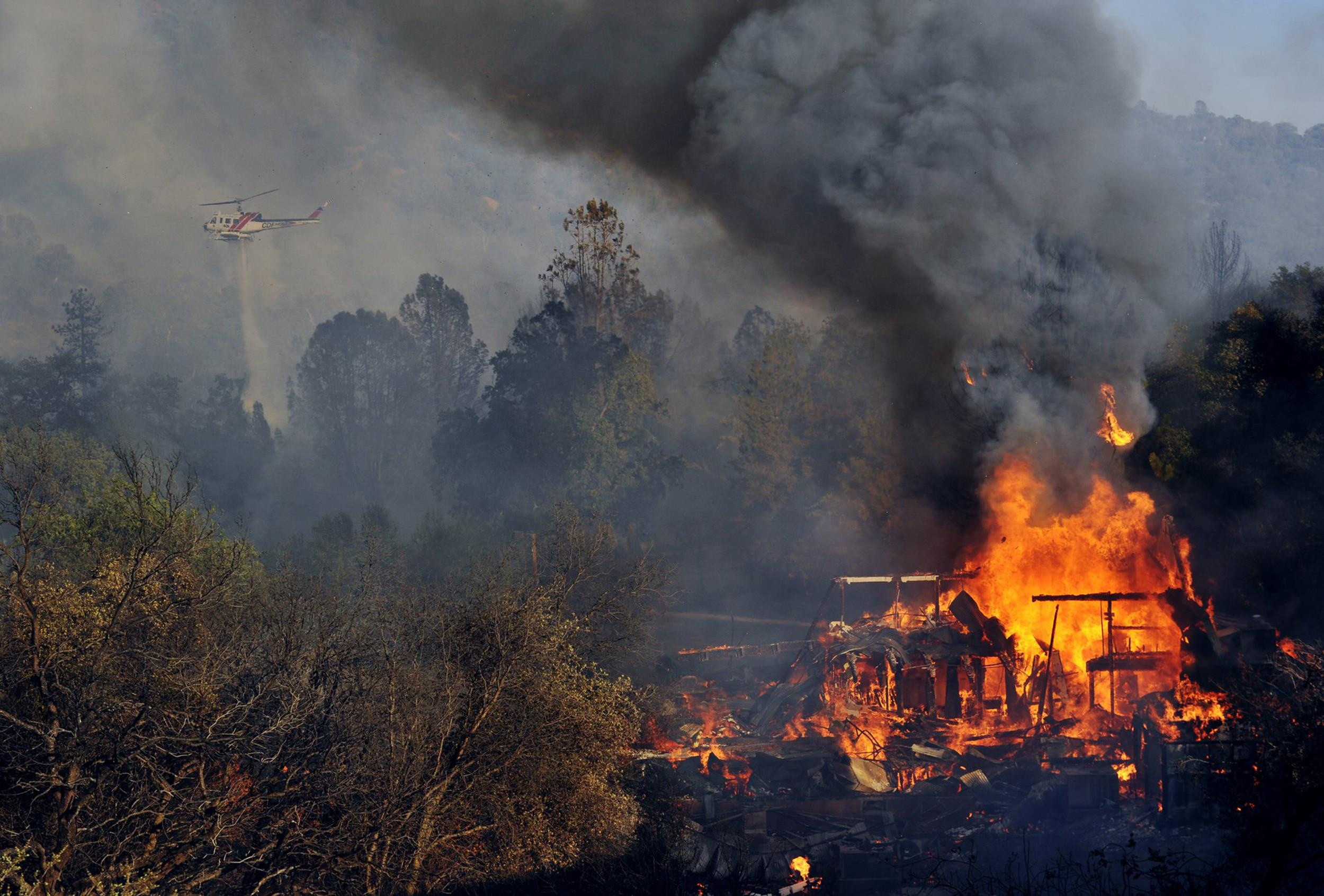 Image: A structure burns along Highway 41 in Oakhurst, Calif., on Aug. 18