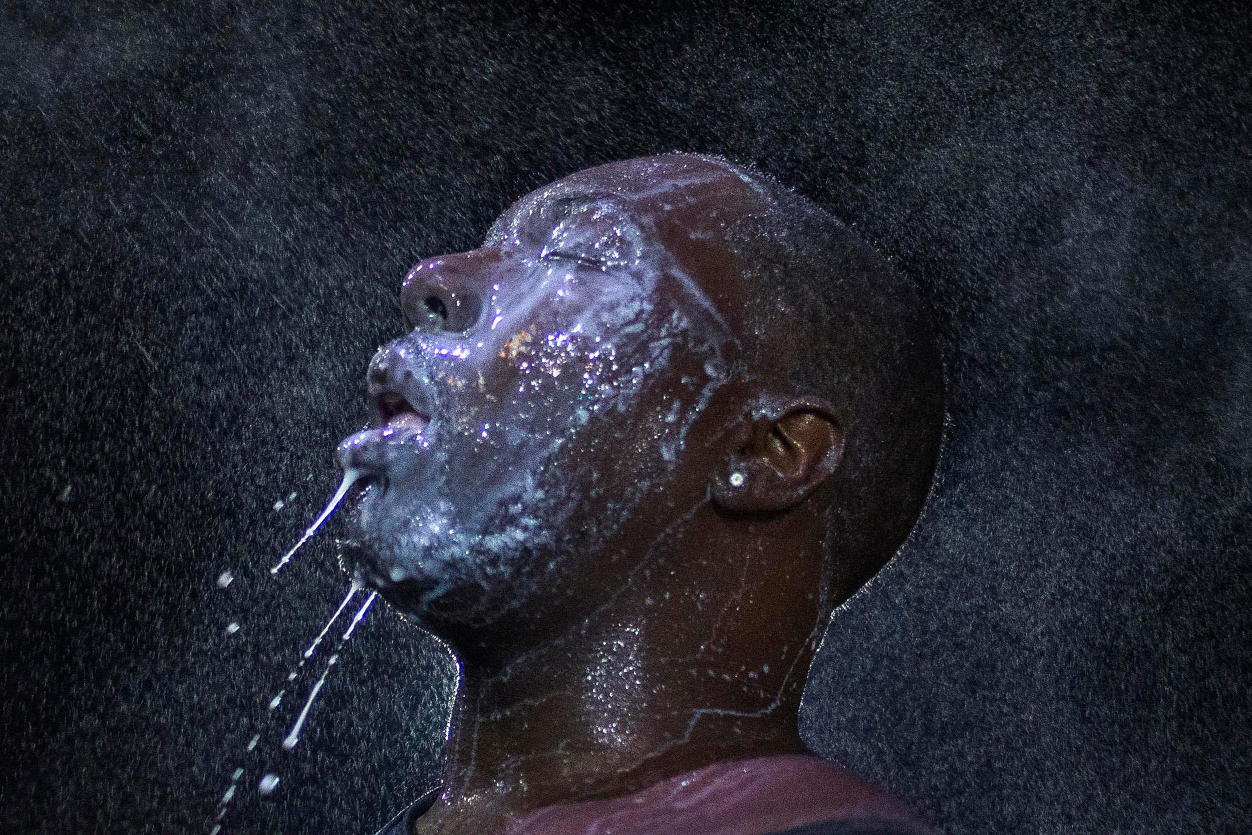 Image: A man is doused with milk and sprayed with mist after being hit by an eye irritant from security forces trying to disperse demonstrators protesting against the shooting of Brown in Ferguson