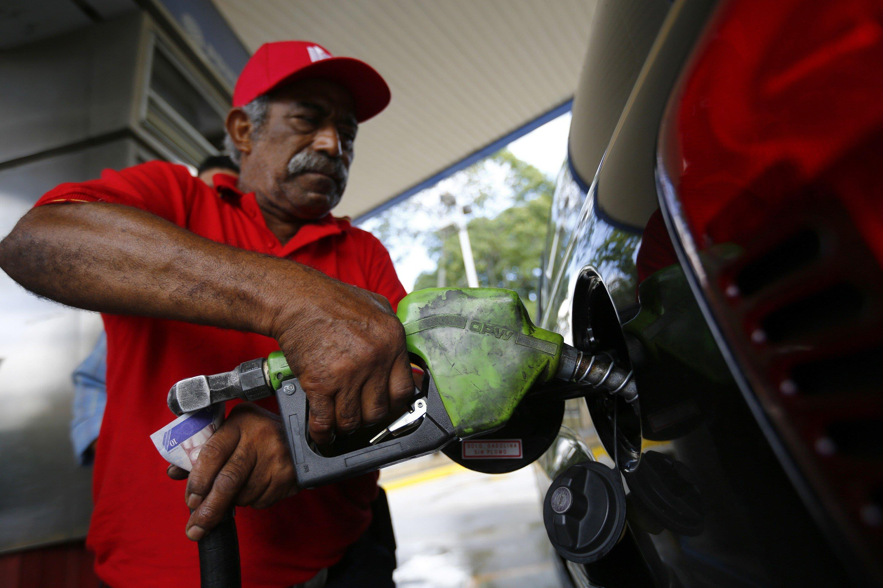 Image: A man pumps gasoline at a service station in Caracas