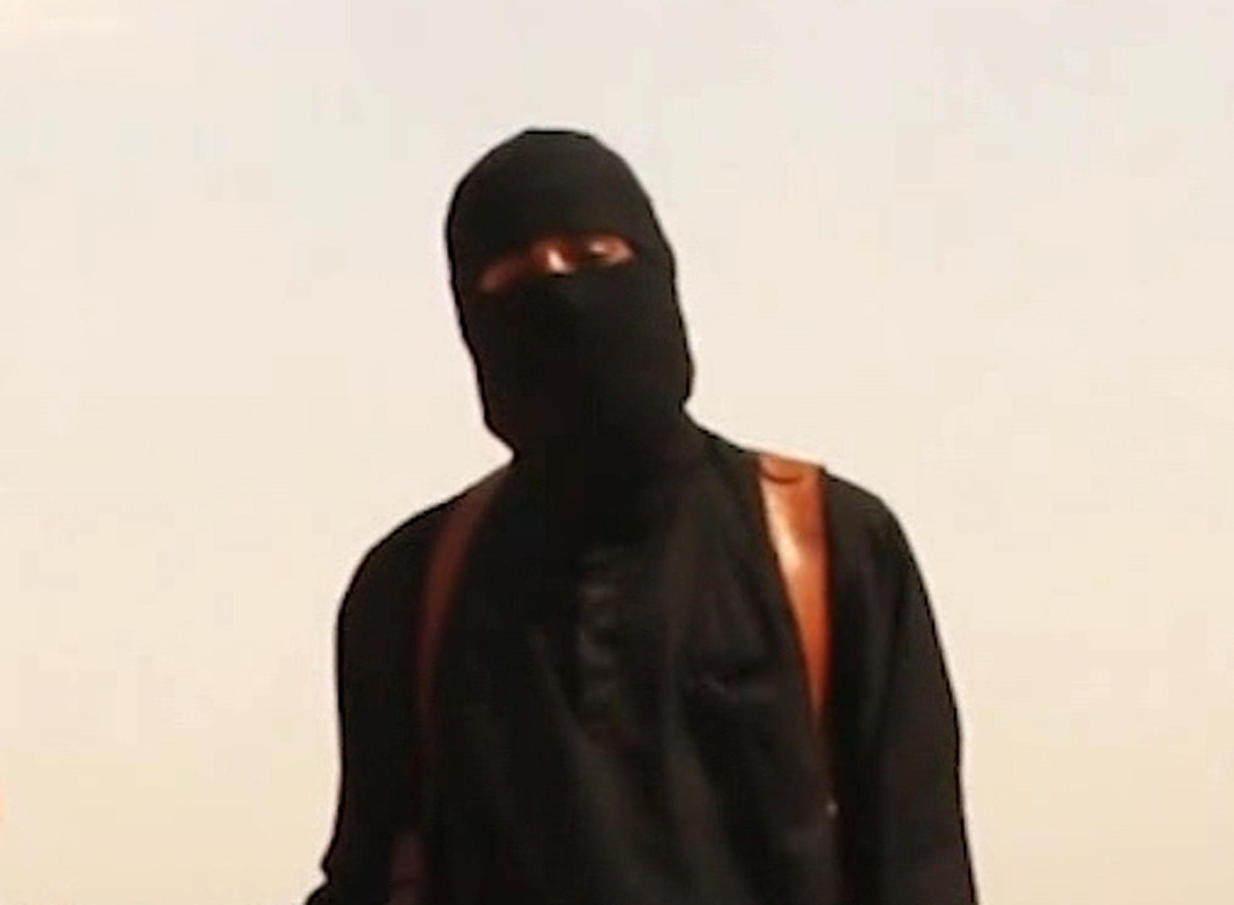 Image: An ISIS militant stands next to James Foley in a video released by the group.