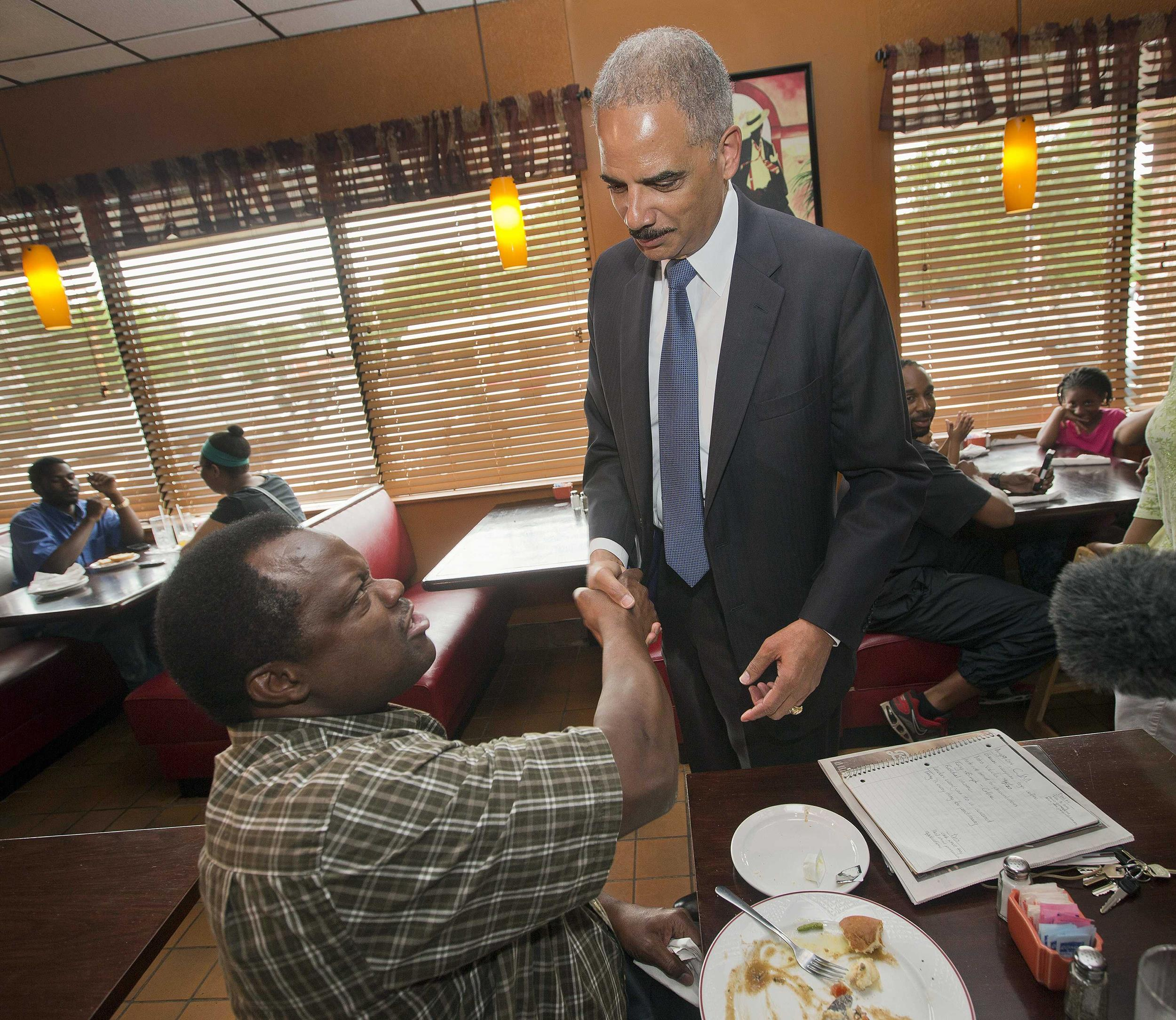 Image: Attorney General Eric Holder shakes hands with a patron before his meeting with community leaders, at Drake's Place Restaurant in Florrissant