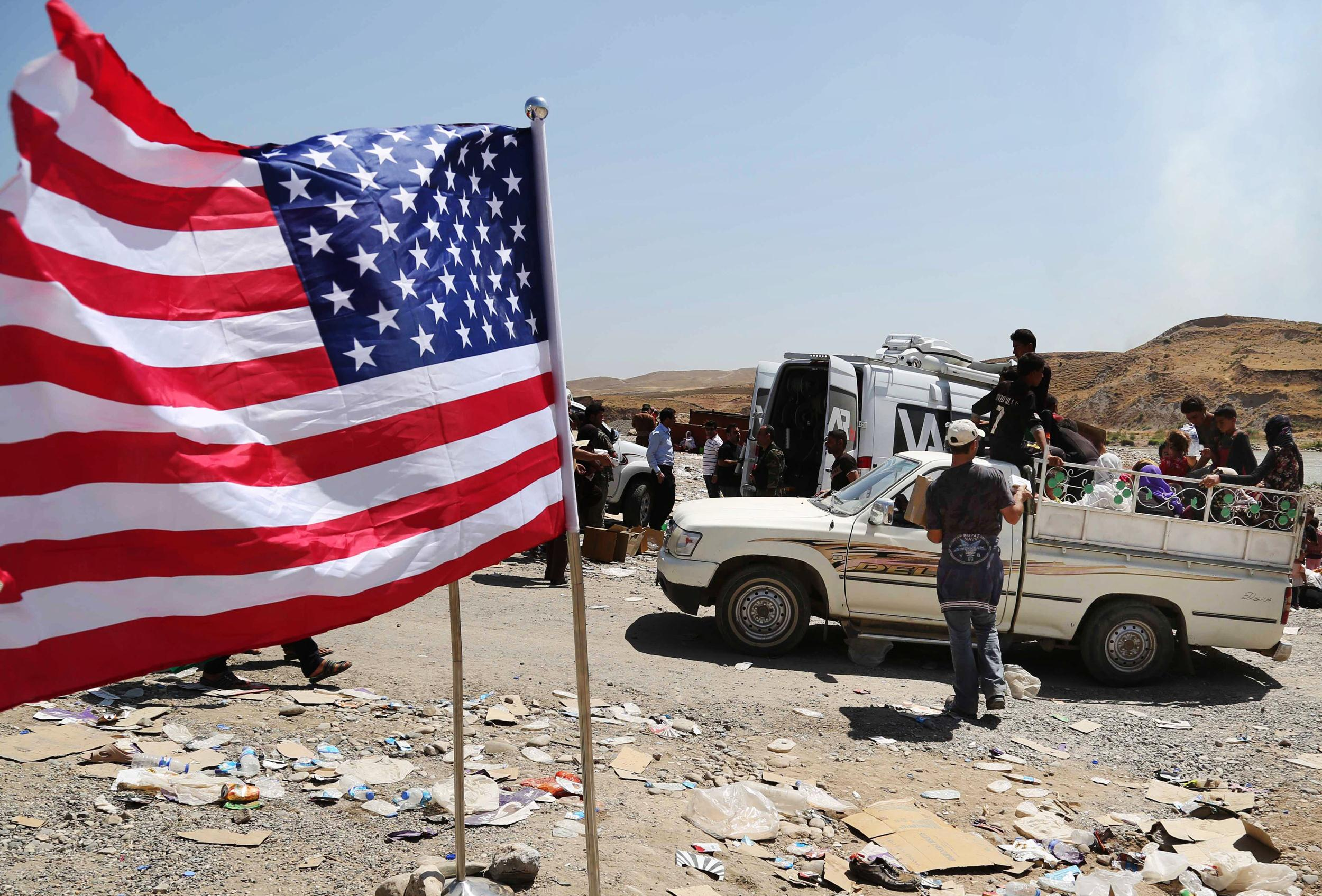Image: A U.S. flag waves while displaced Iraqis from the Yazidi community cross the Syria-Iraq border