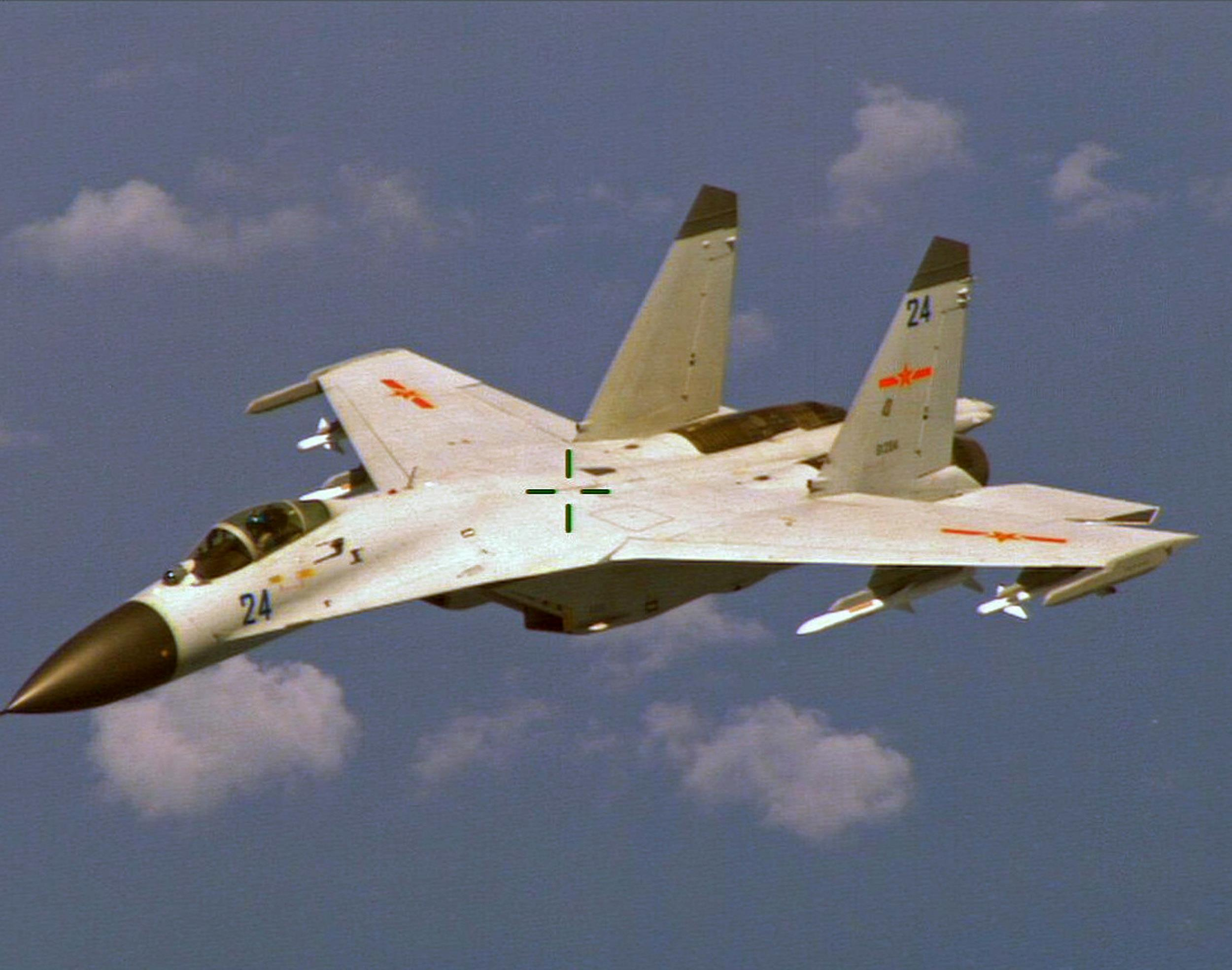 Image: A Chinese J-11 fighter jet is seen flying near a U.S. Navy P-8 Poseidon east of China's Hainan Island