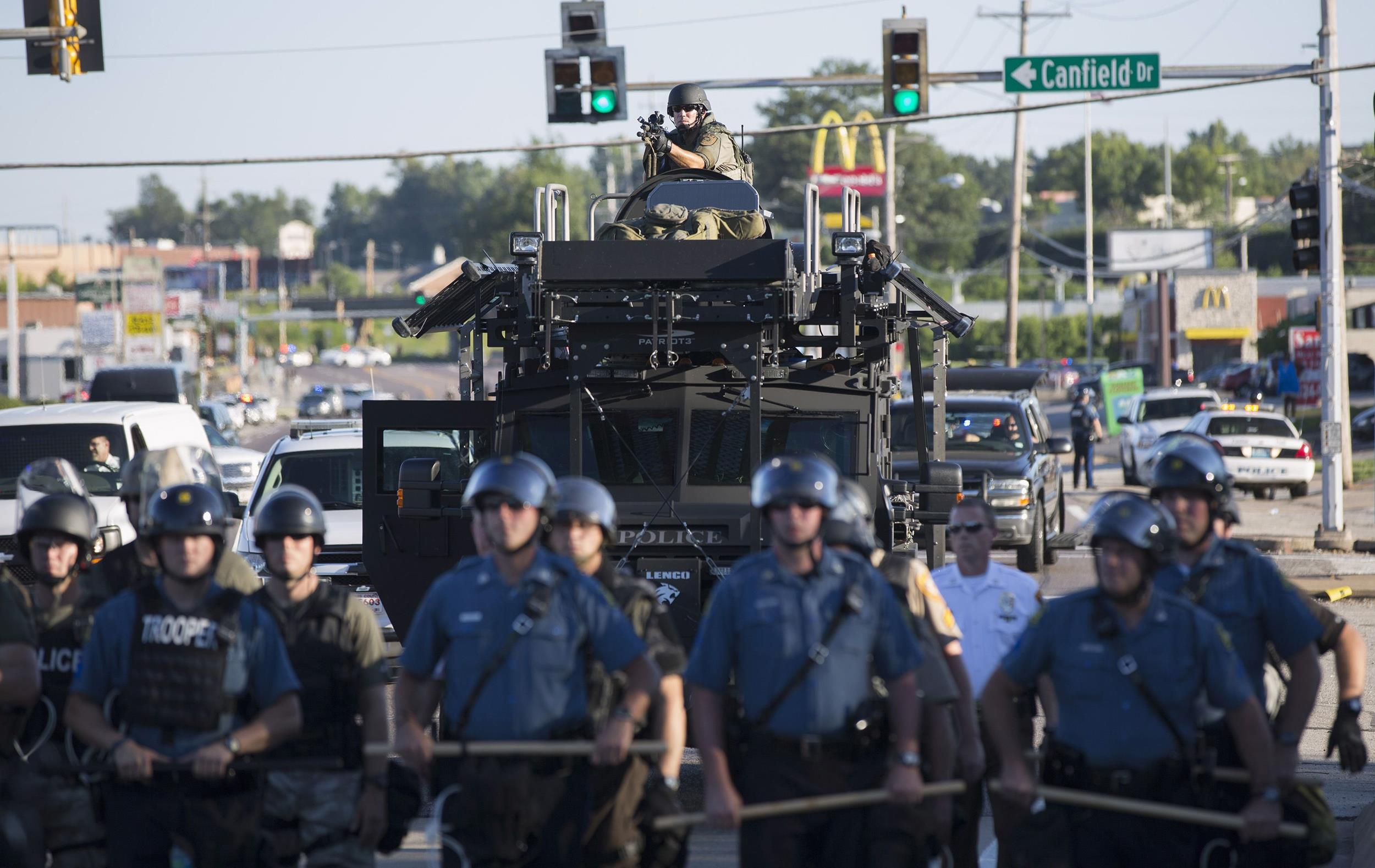 Image: Riot police stand guard as demonstrators protest the shooting death of teenager Michael Brown in Ferguson, Missouri