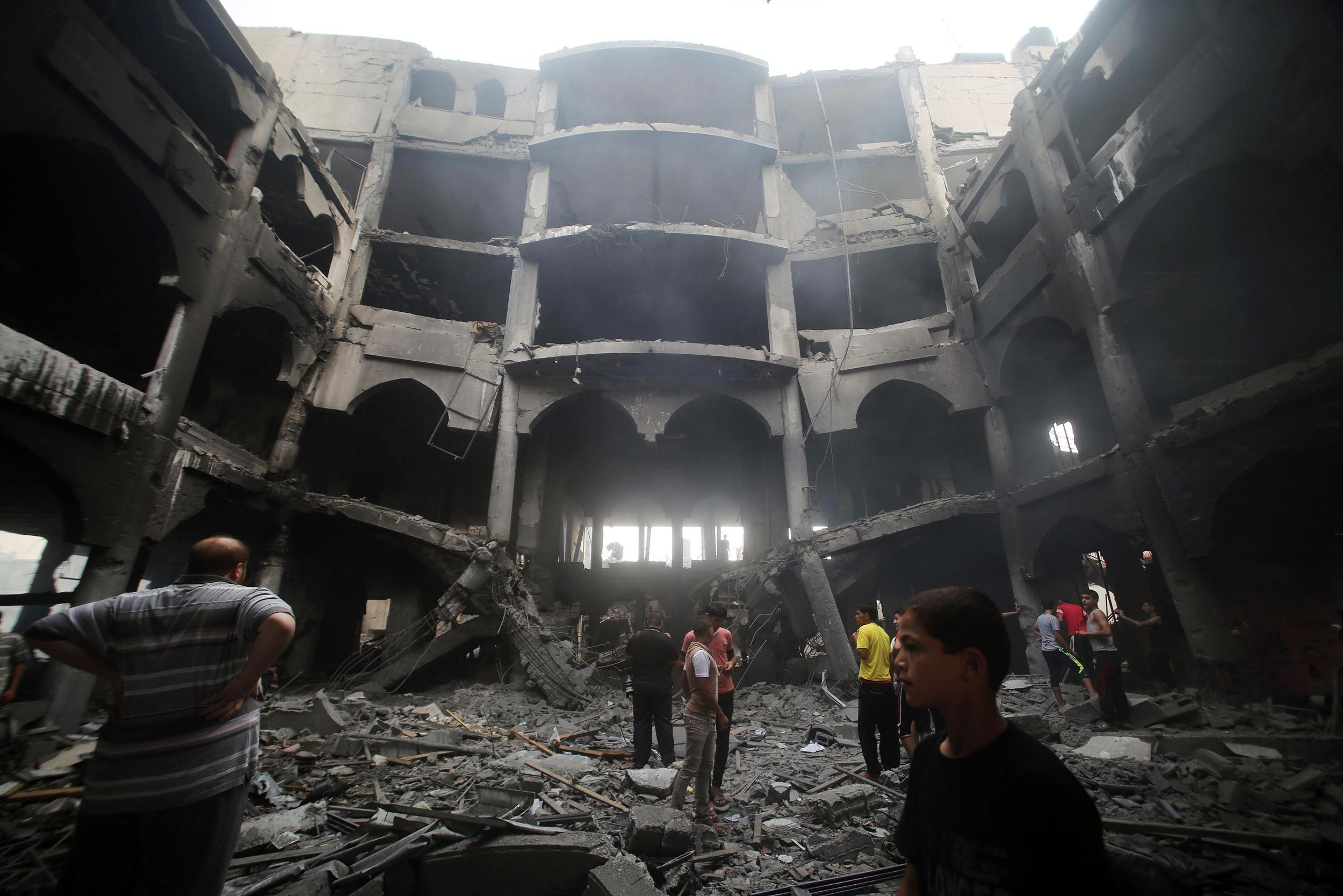 Image: Palestinians inspect the rubble of a shopping center