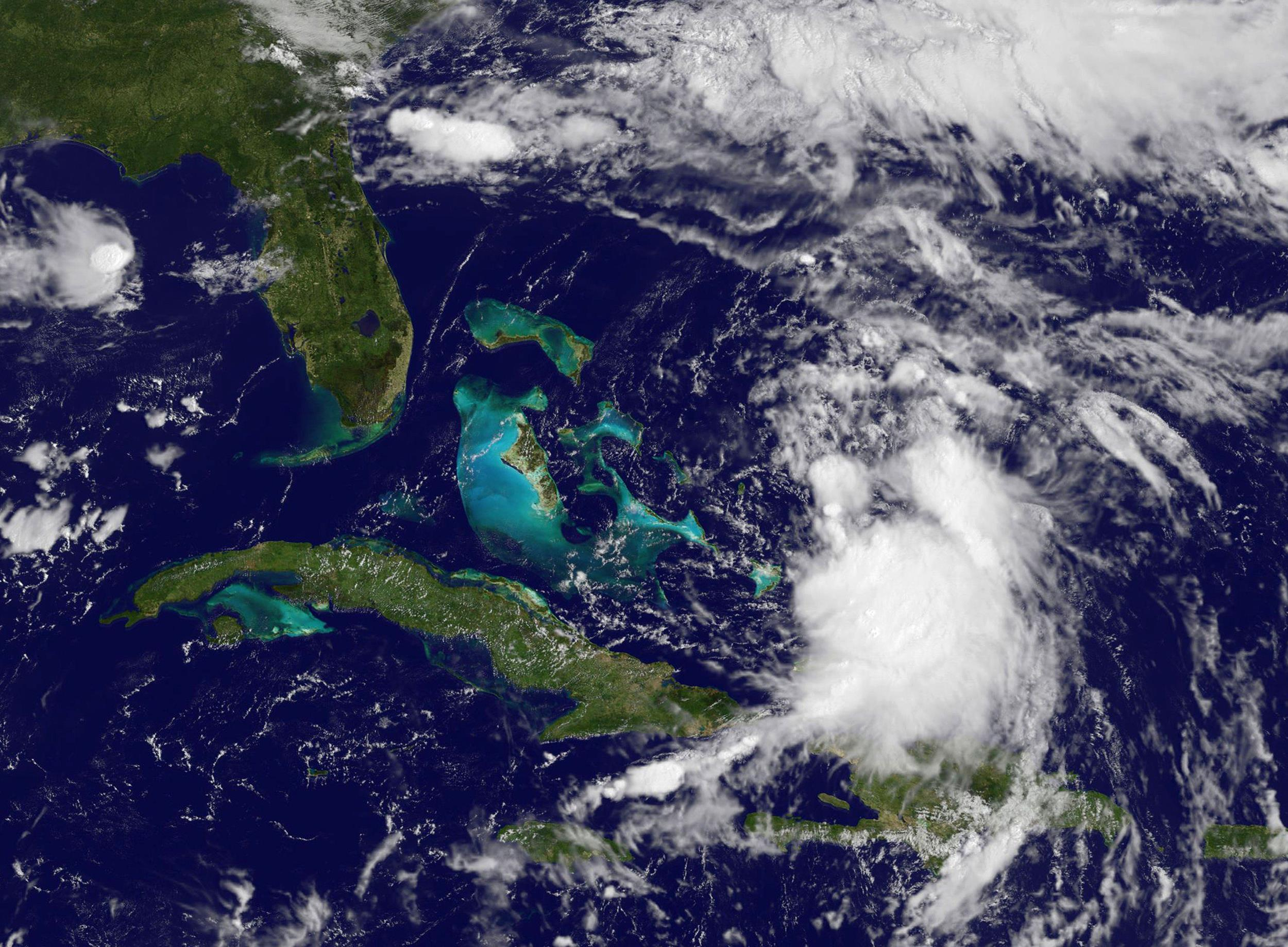 Image: NASA GOES satellite image shows Tropical Storm Cristobal(Lower-R) forming near the Bahamas.
