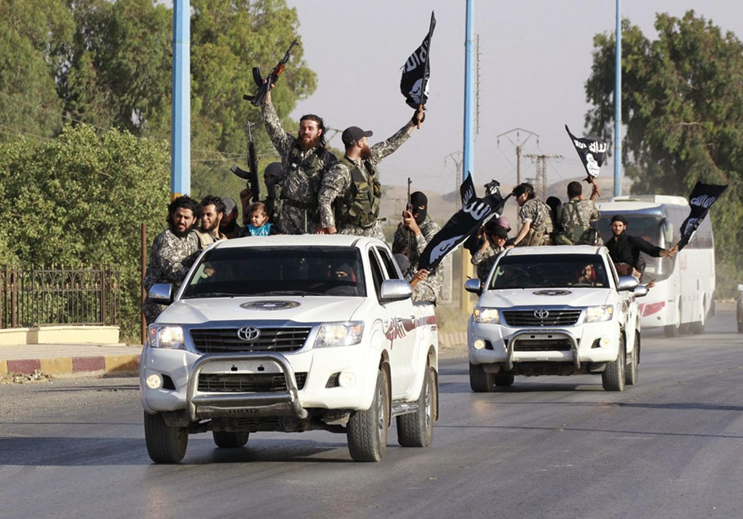 Image: Militant Islamist fighters wave flags as they take part in a military parade along the streets of Raqqa