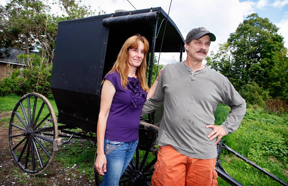 Image: Jeffrey M. and Pamela L. Stinson pose for a portrait outside an Amish buggy