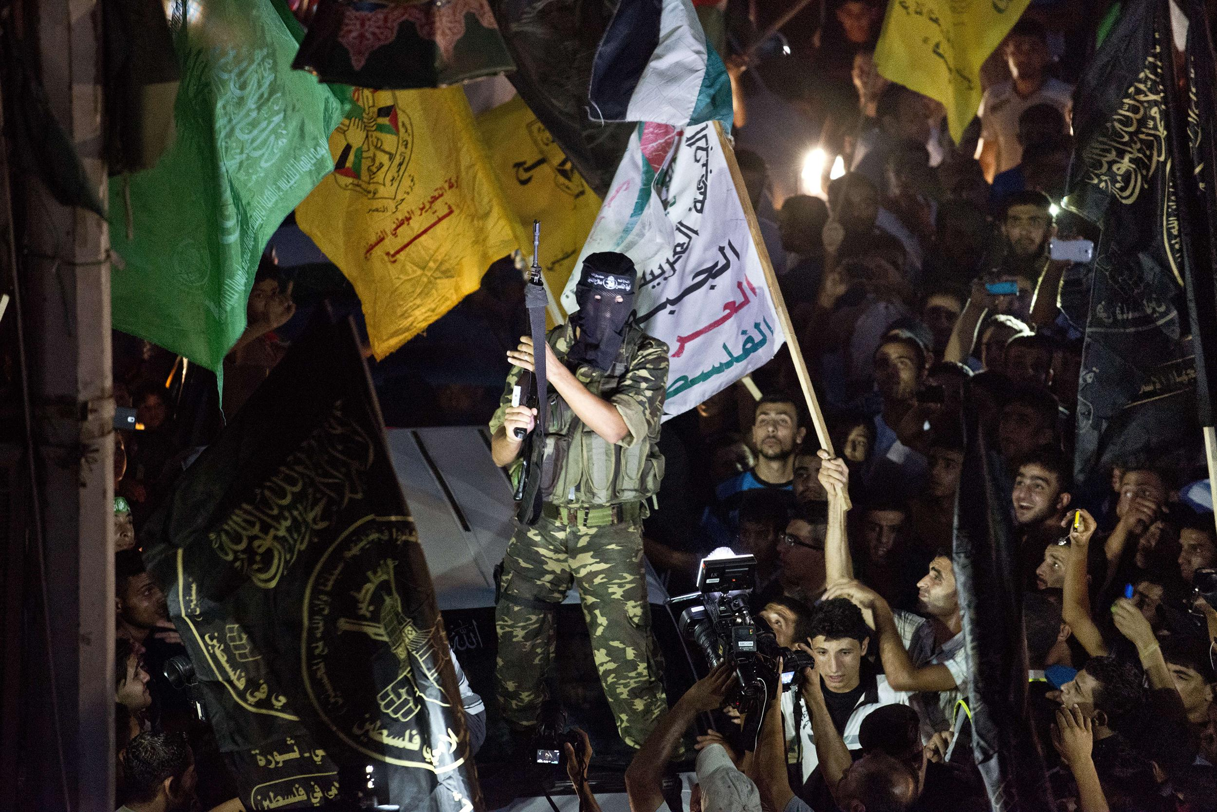 Image:A Hamas militant brandishes his weapon as he fires rounds into the air after joining hundreds of Gazans gathered at an intersecition in Gaza City on Aug. 26,