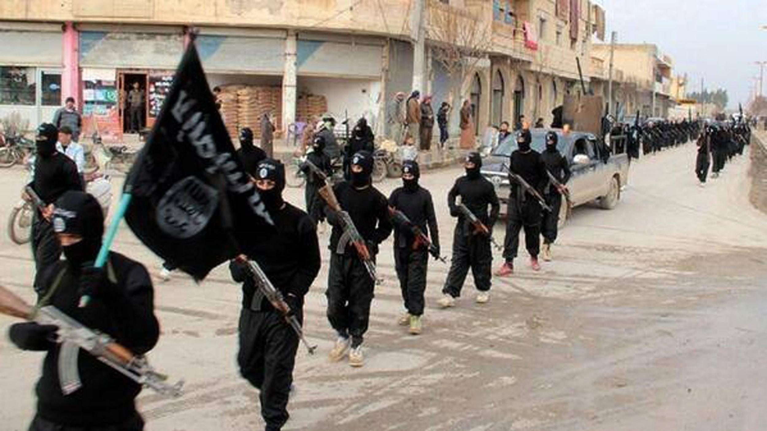 Image: Fighters from the al-Qaida linked Islamic State of Iraq and Syria (ISIS) march in Raqqa, Syria.