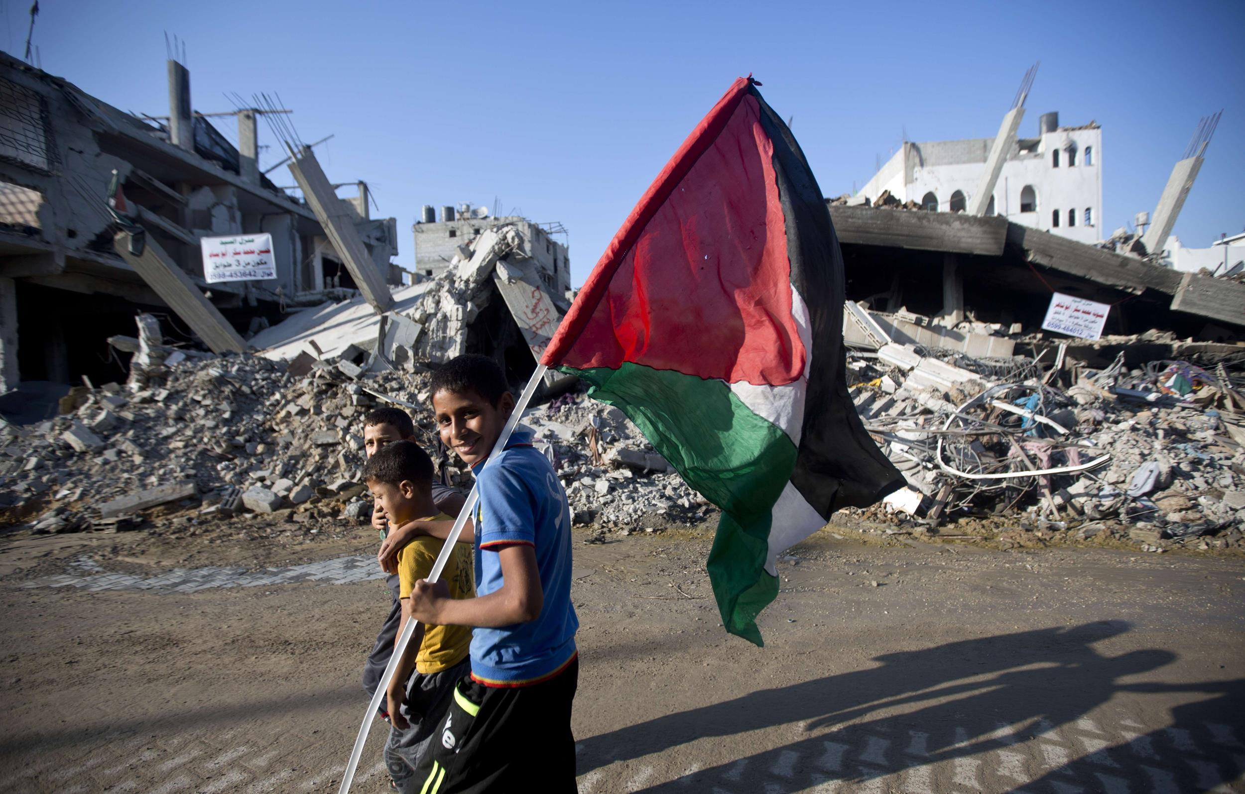 Image: A group of Palestinian boys, one carrying the national flag, walk past destroyed houses in the Shejaiya neighborhood of Gaza City