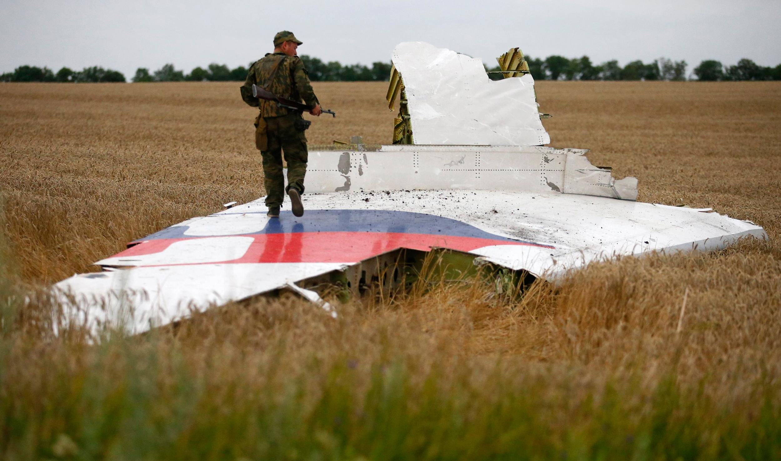 Image: An armed pro-Russian separatist stands on part of the wreckage of the Malaysia Airlines Boeing 777 plane