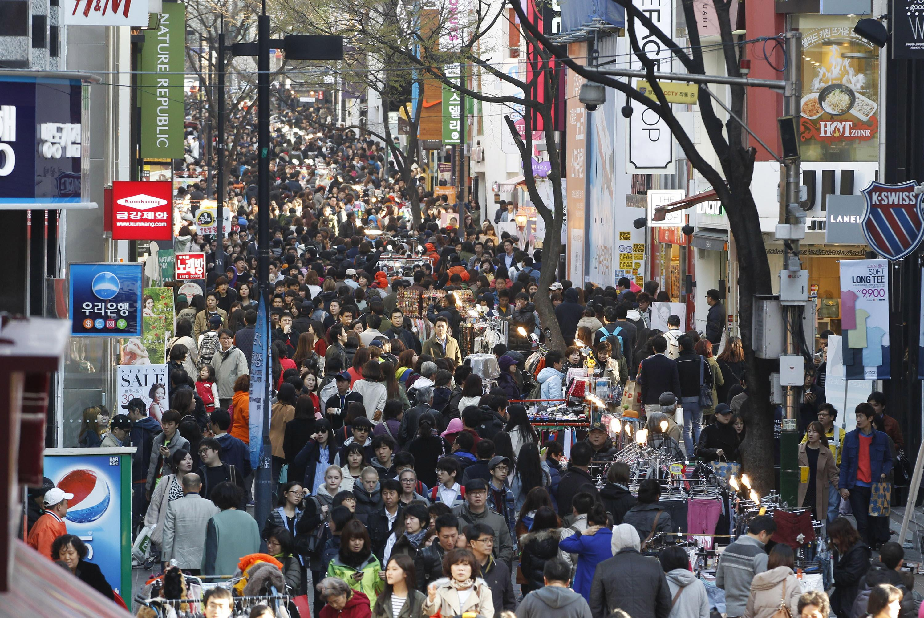Image: People crowd at Myeongdong, a main shopping street, for weekend shopping.