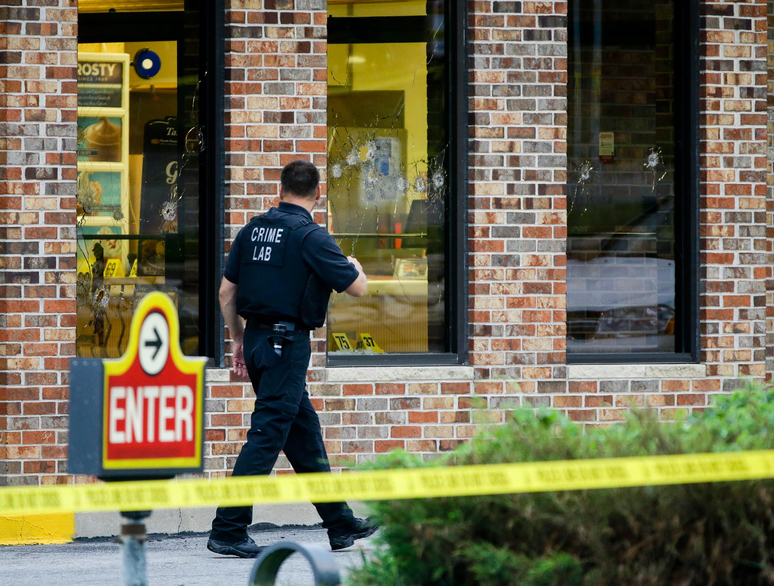 Image: A crime lab technician walks past bullet riddled windows at a Wendy's in Omaha, Neb.
