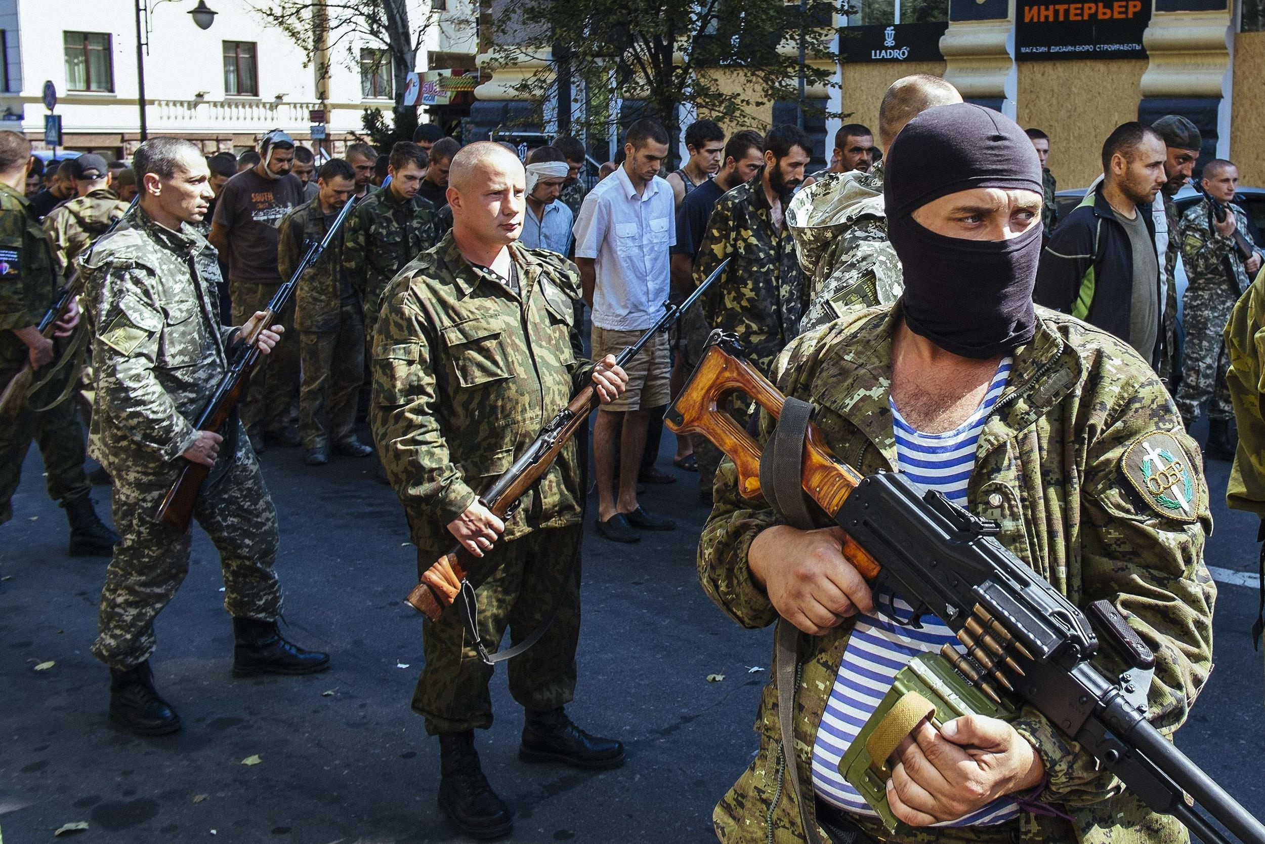 Image: Pro-Russian gunmen guard parade dozens of captured Ukrainian soldiers during a march  in mockery of the country's Independence Day celebrations  in the main separatist stronghold Donetsk