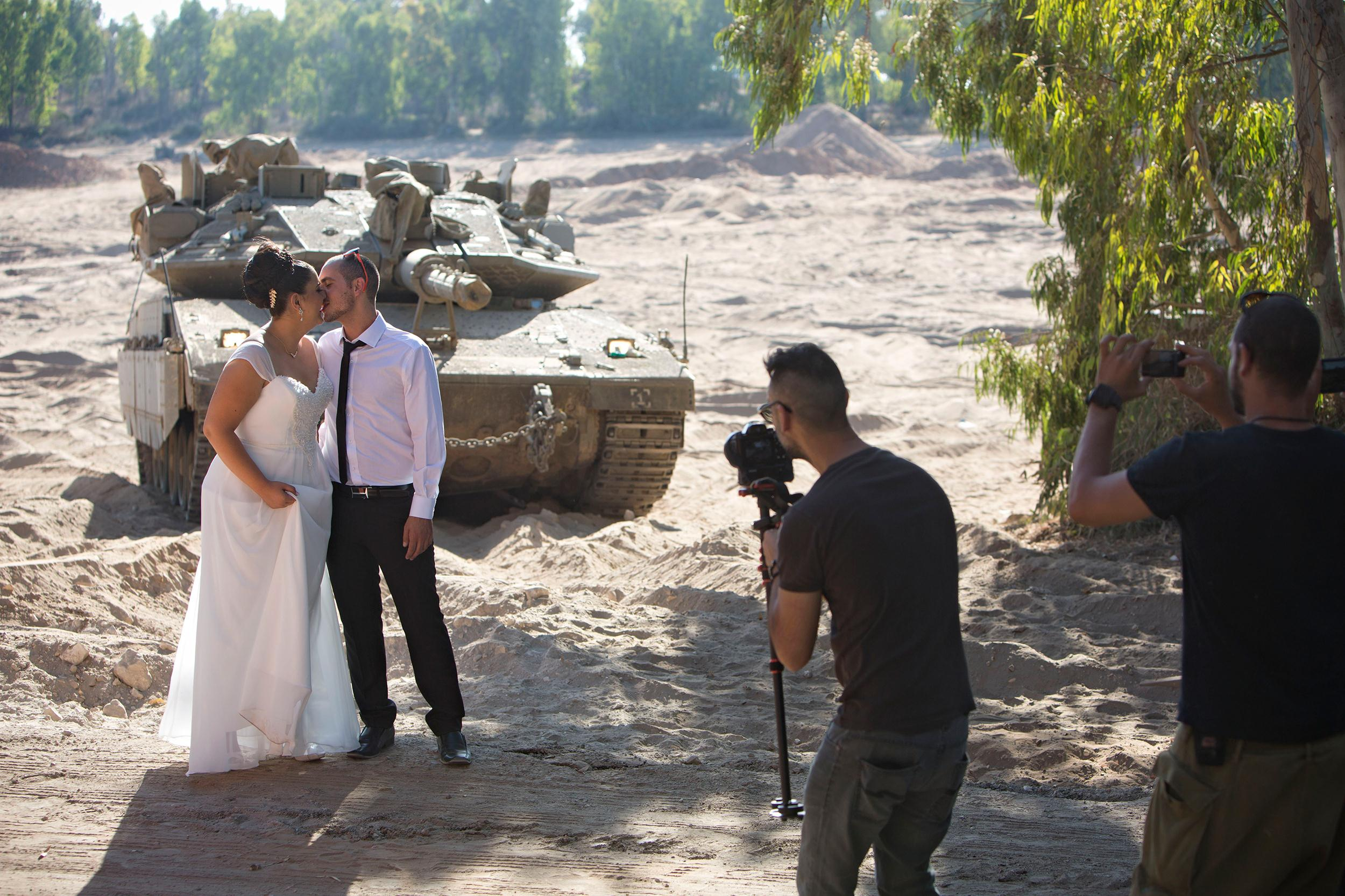 Image: Israeli couple, Noga and Moshiko Siho, have their wedding photo taken in an army staging area on the Israeli Gaza border, near Kibbutz Yad Mordechai, Israel