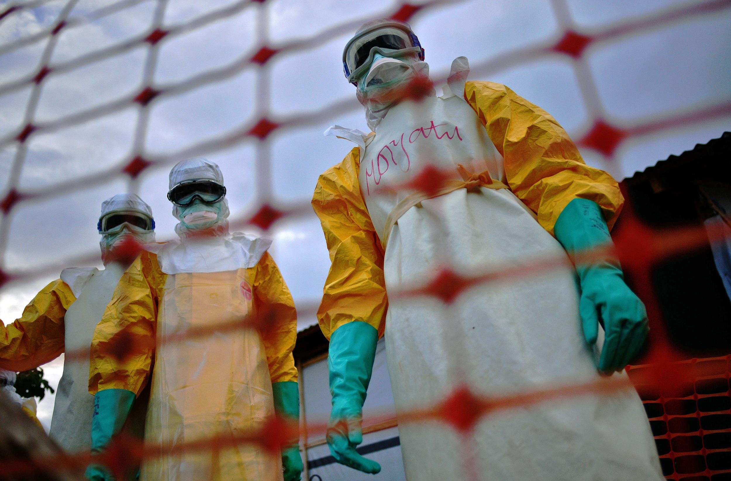 Image: Medecins Sans Frontieres (MSF) medical staff wearing protective clothing treat the body of an Ebola victim