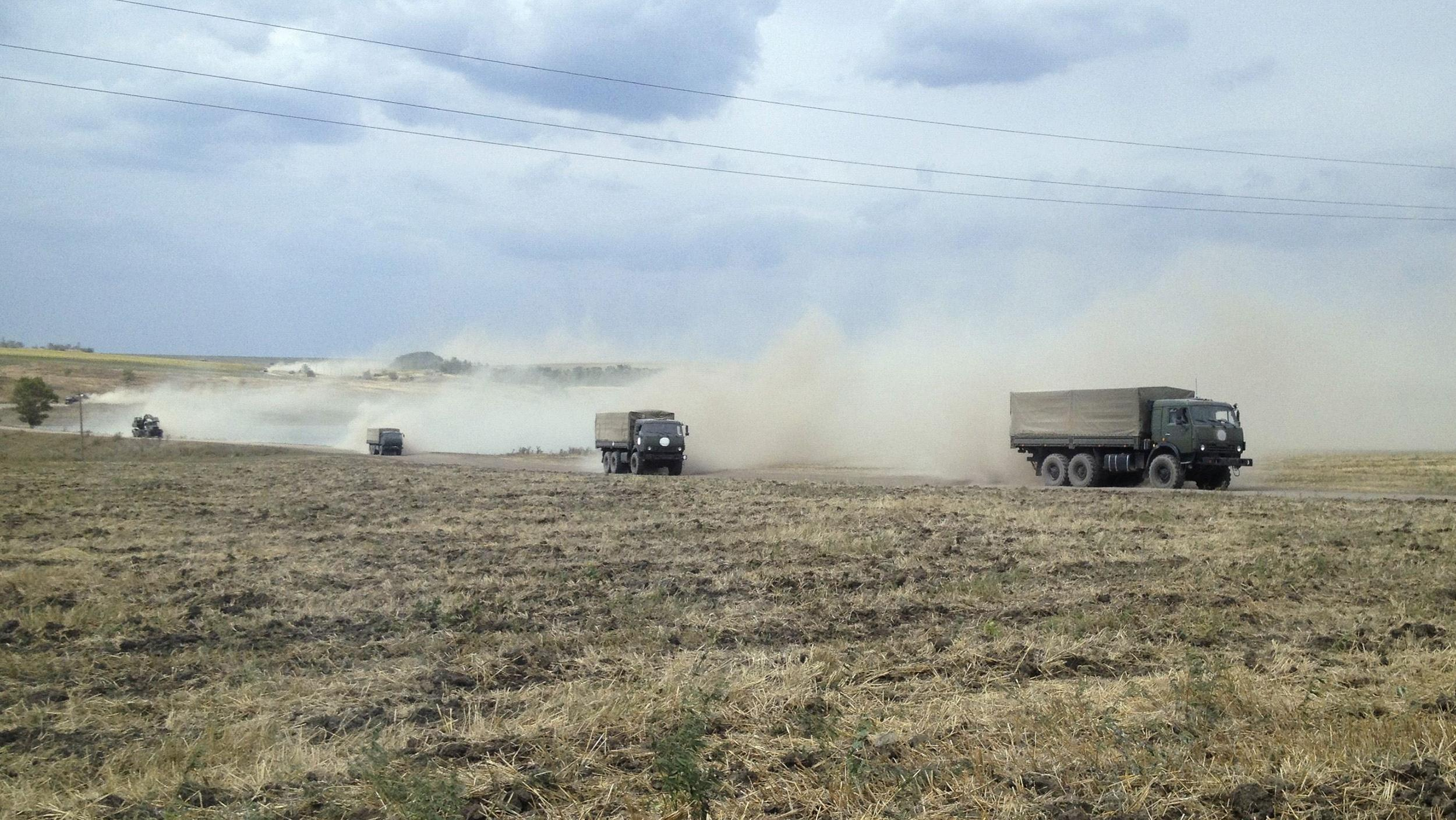 Image: Military trucks travel through the steppe near the village of Krasnodarovka