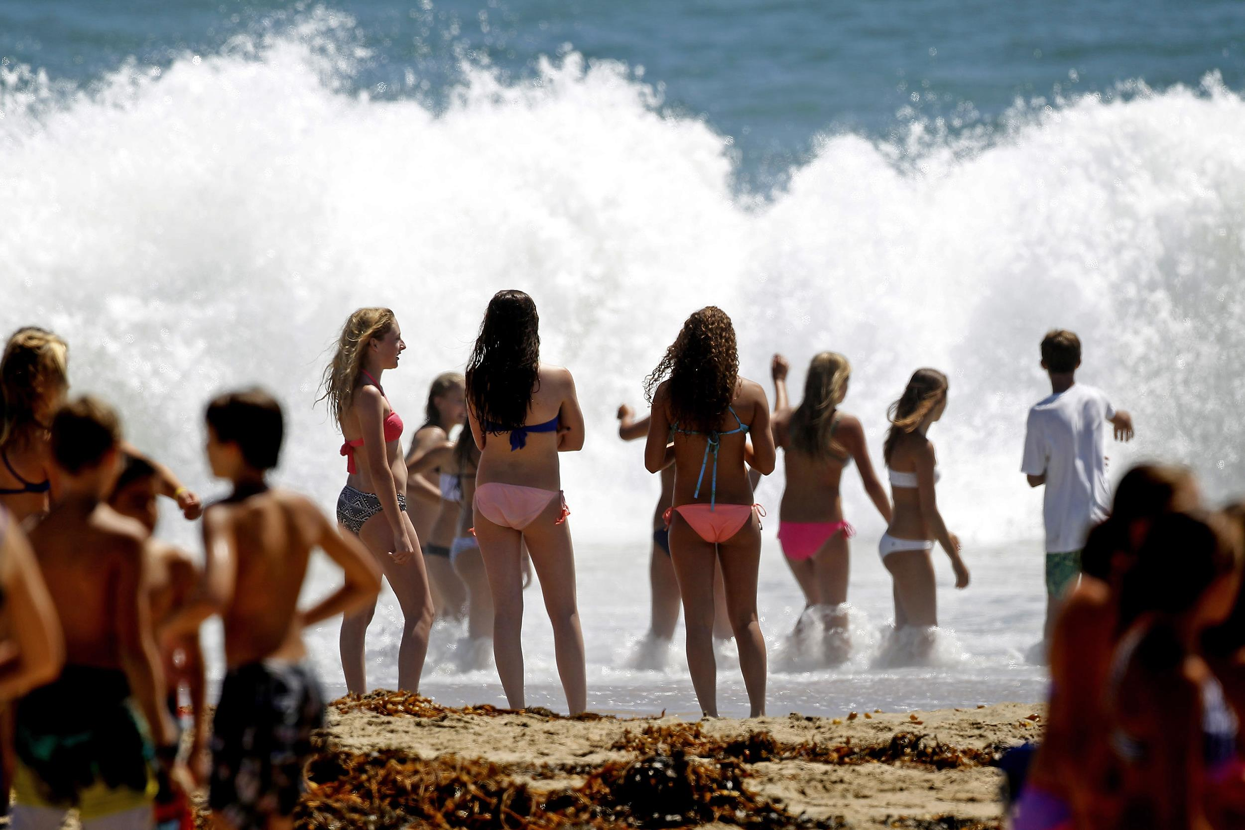 Image: Beachgoers watch large waves crash on the shore at Seal Beach, Calif., on Aug. 26.