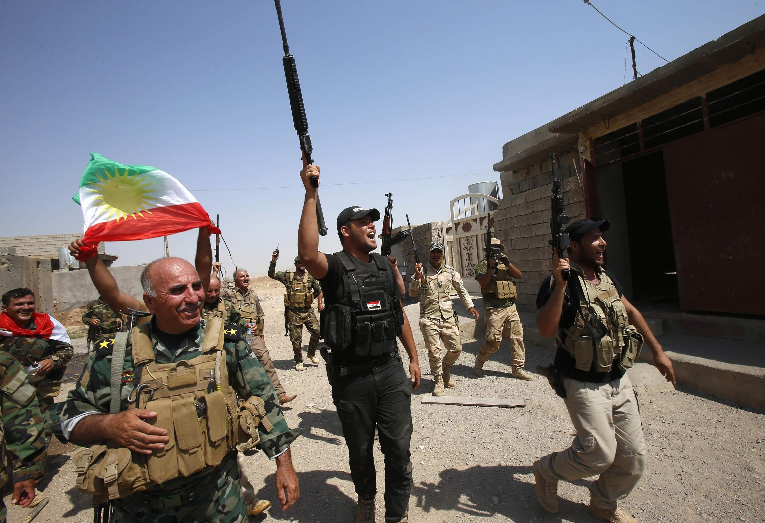 Image: Kurdish peshmerga forces celebrate as they take control of Sulaiman Pek from the Islamist State militants, in the northwest of Tikrit city