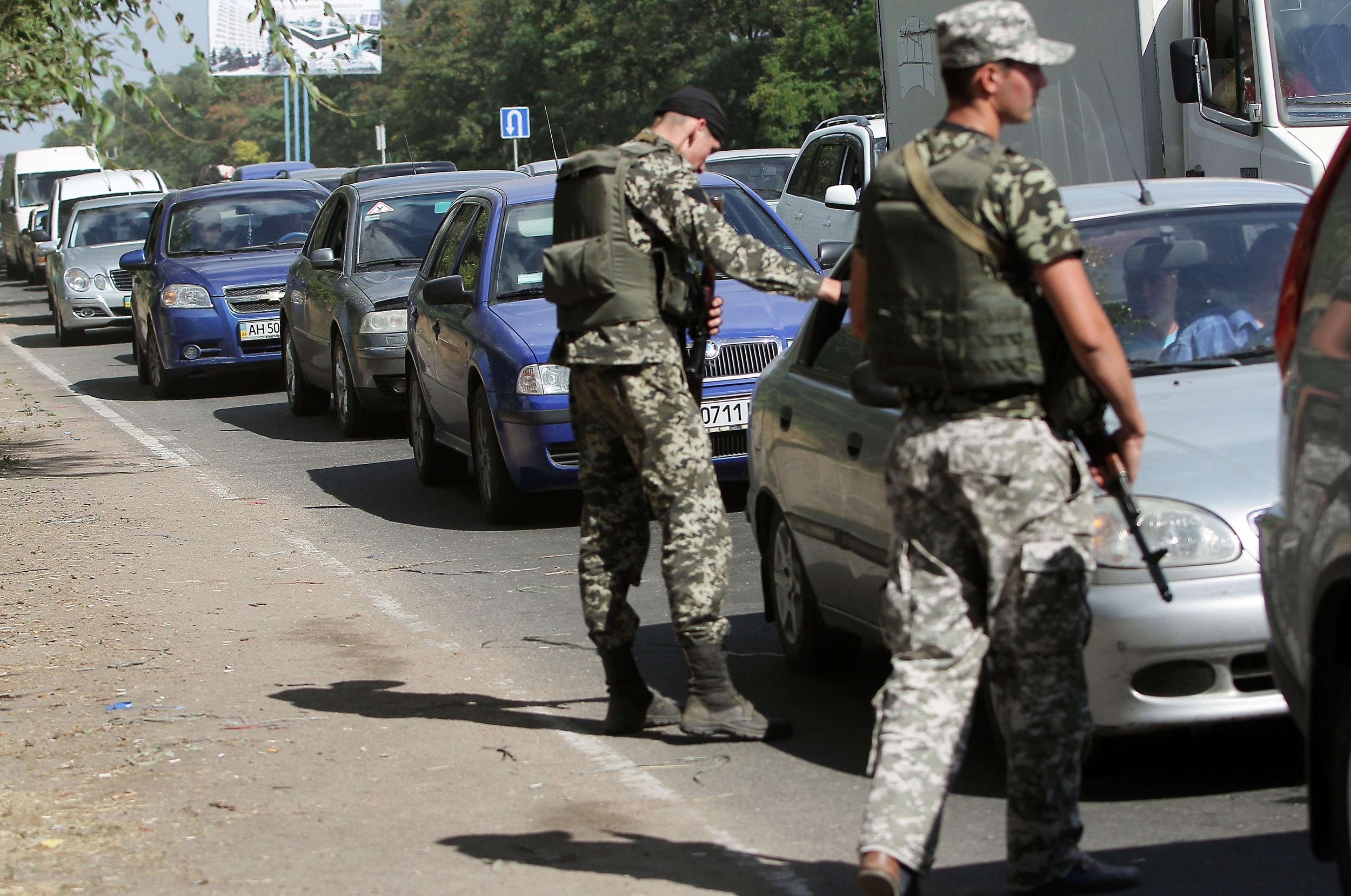 Image: Ukrainian troops stop cars at a checkpoint as people flee the southern Ukrainian city of Mariupol