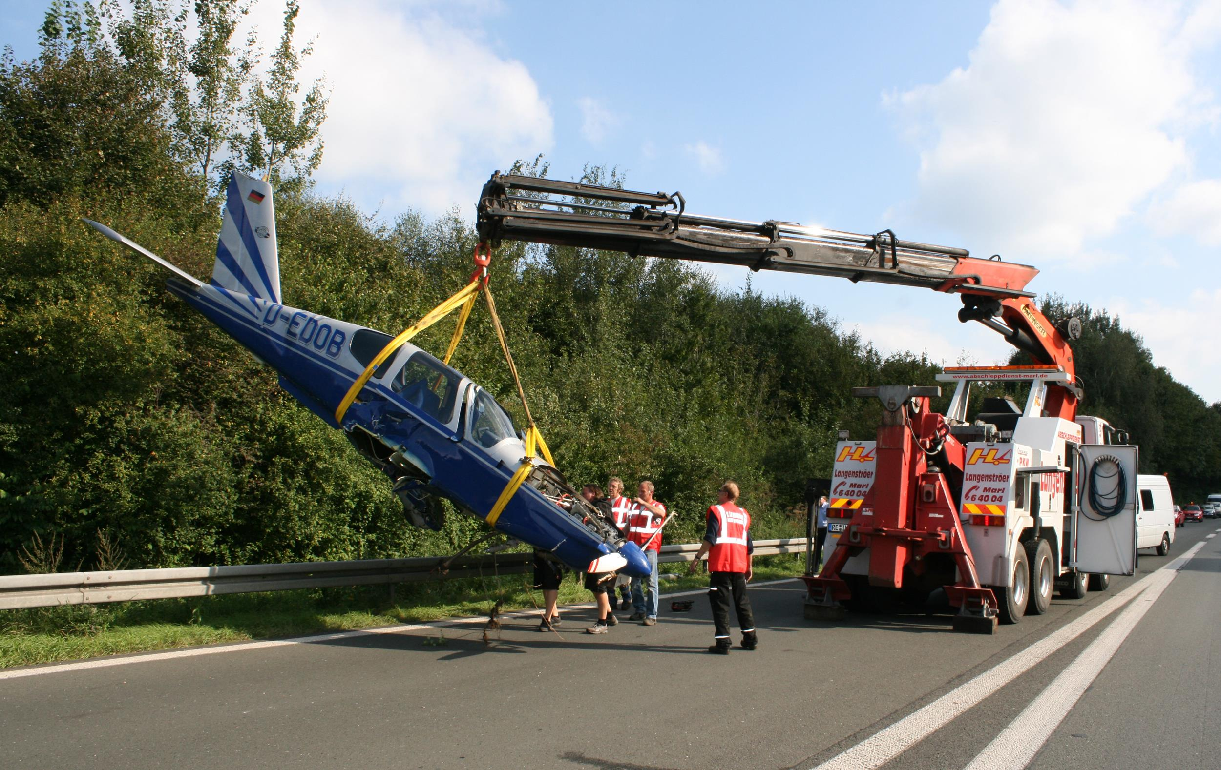 A small plane is recovered after landing beside the A43 Autobahn in northern Germany.