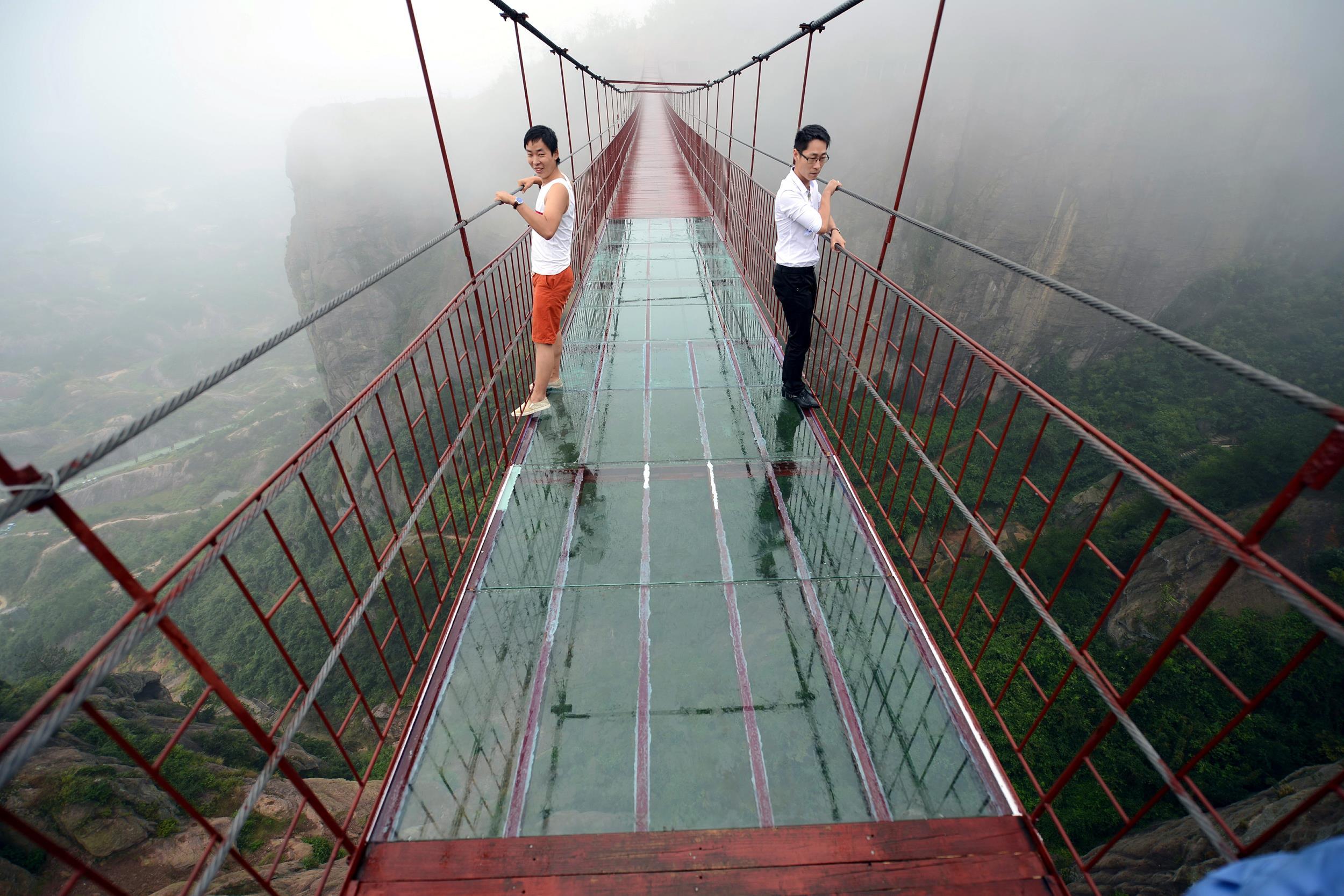 Tourists tiptoe across transparent bridge in china nbc news for Suspension transparente