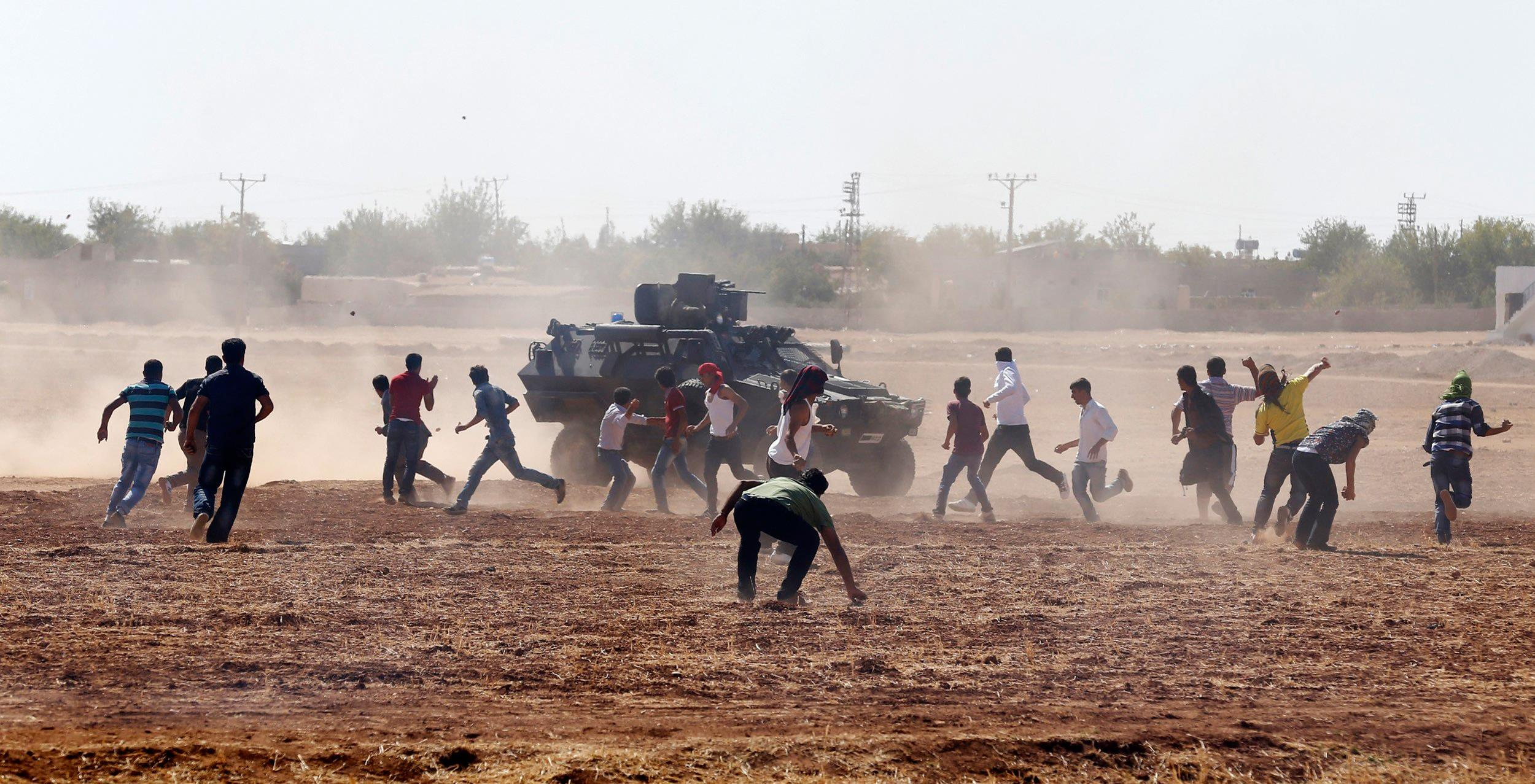 Image protesters throw stones at an armoured army vehicle during a