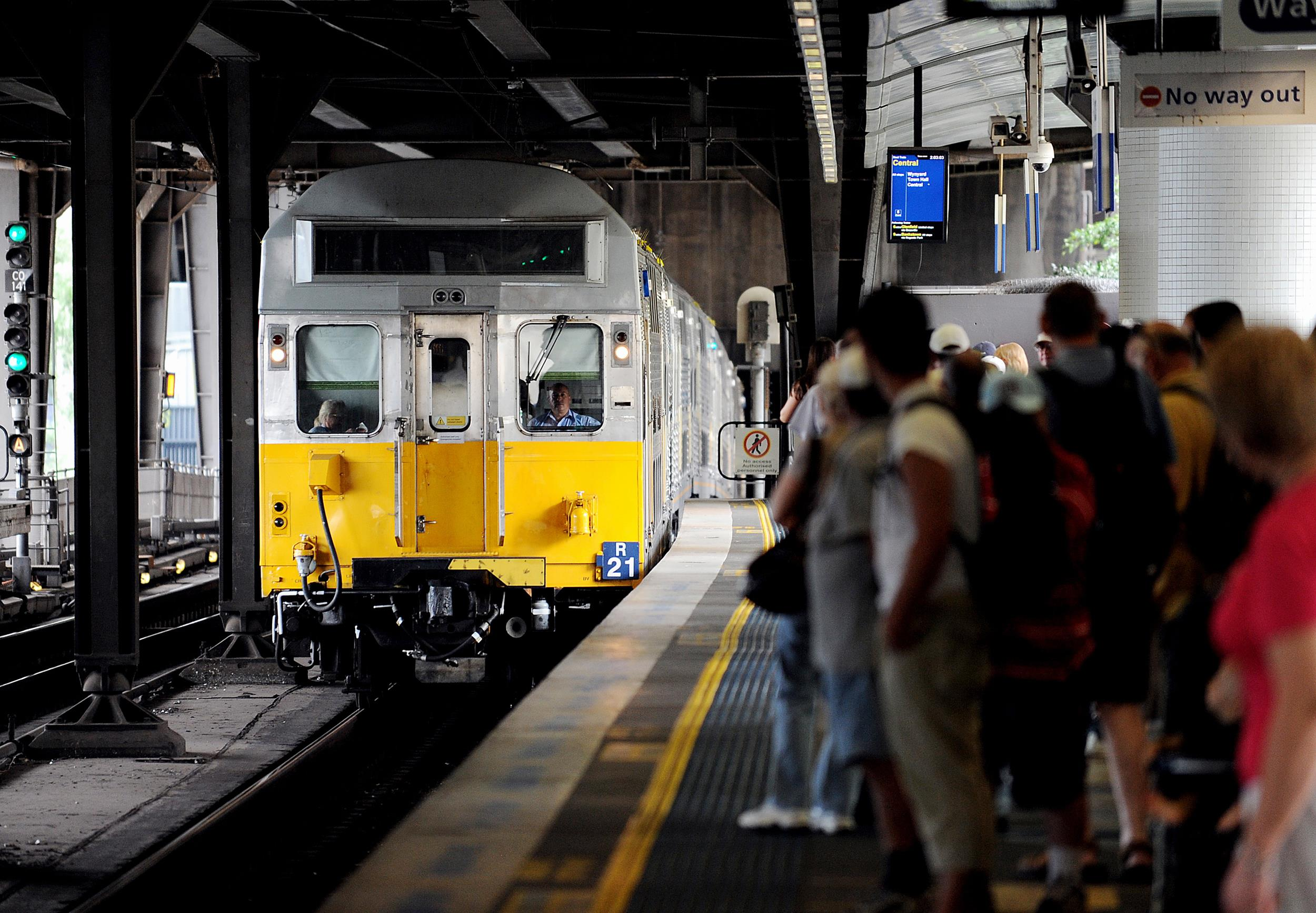 Commuters wait as a New South Wales Government CityRail commuter train