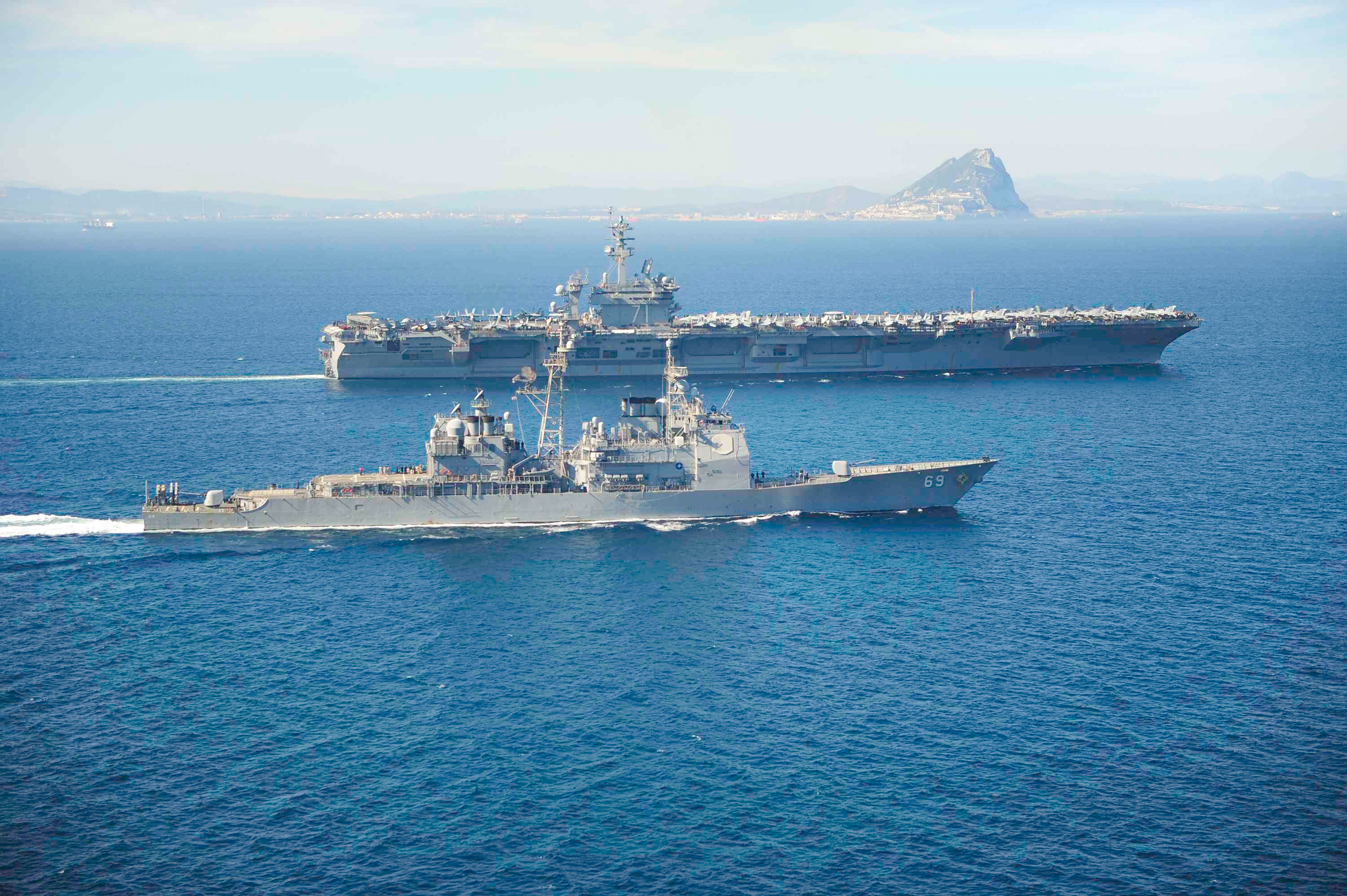 Image:  USS Theodore Roosevelt carrier, top, passes the Rock of Gibraltar in the Mediterranean Sea